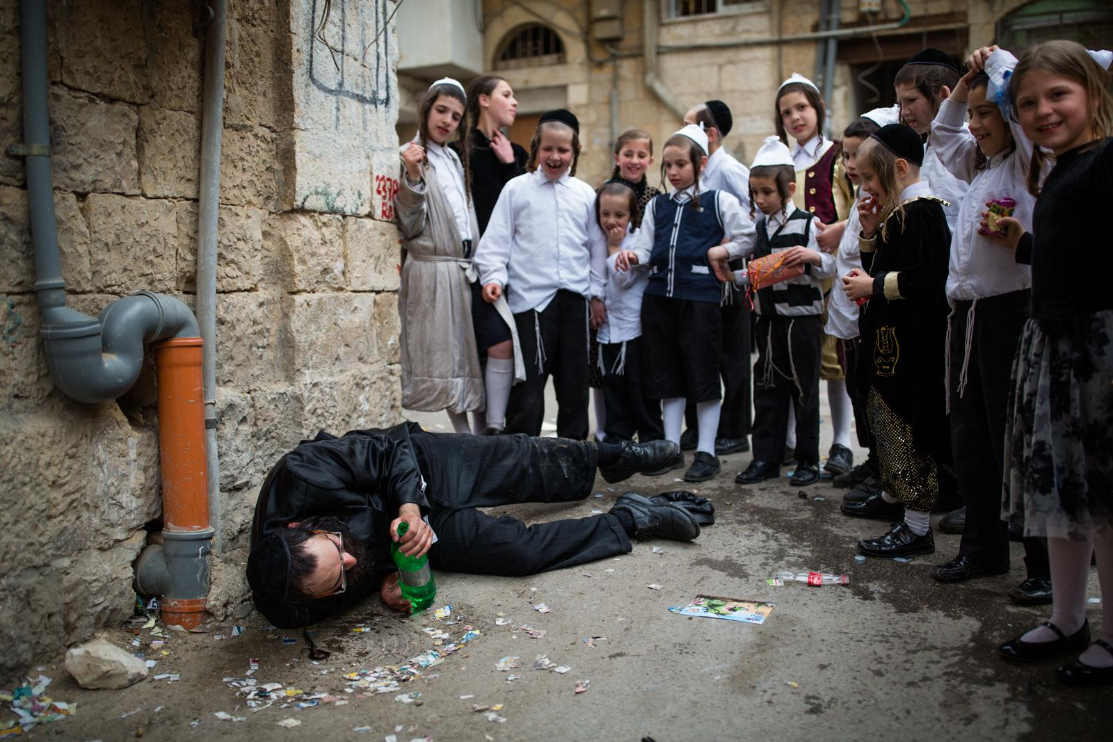 JERUSALEM, ISRAEL - MARCH 25, 2016: Ultra Orthodox Jews celebrate the Jewish holiday Purim in the streets of the ultra orthodox Jewish neighborhood of Meah Shearim, March 25, 2016, The Jewish holiday of Purim commemorates the Jews' salvation from genocide in ancient Persia, as recounted in the Book of Esther which is read in synagogues. Other customs include: sending food parcels and giving charity, dressing up in masks and costumes, eating a festive meal, and public celebration.