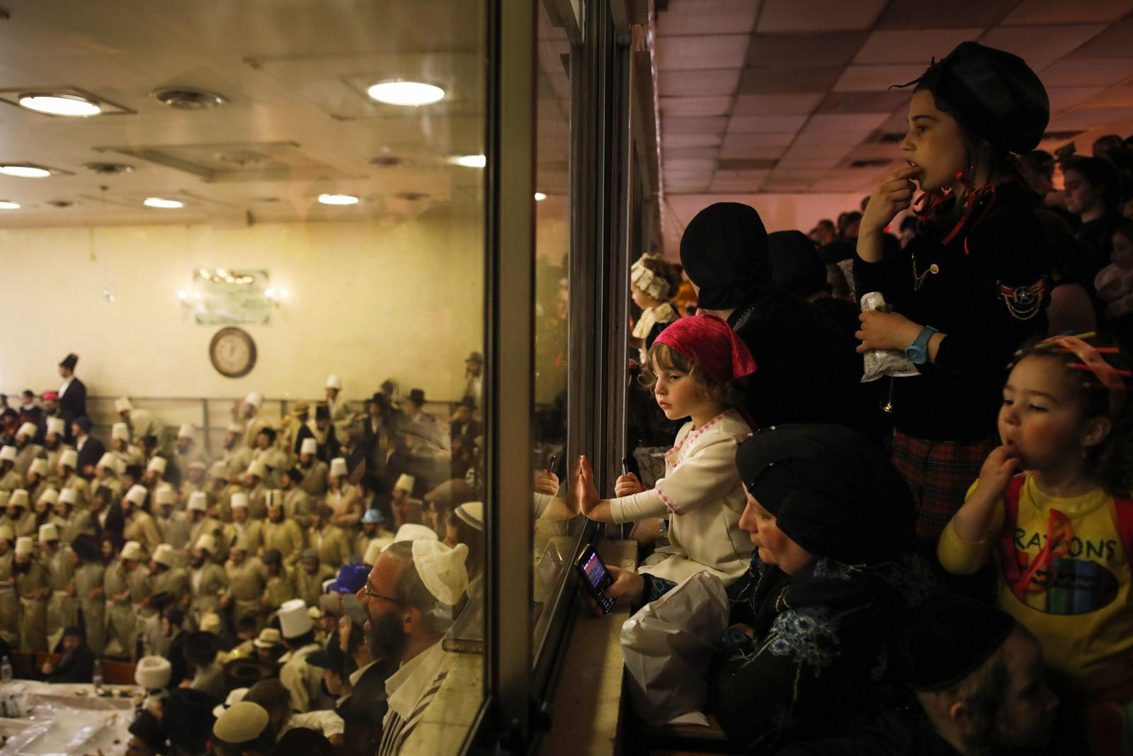 Ultra-Orthodox women and girls are seen in the women's section of a synagogue during the Jewish holiday of Purim in the ultra-orthodox neighbourhood Mea Shearim, Jerusalem, March 22, 2019. The Jewish holiday of Purim commemorates the Jews' salvation from genocide in ancient Persia, as recounted in the Book of Esther