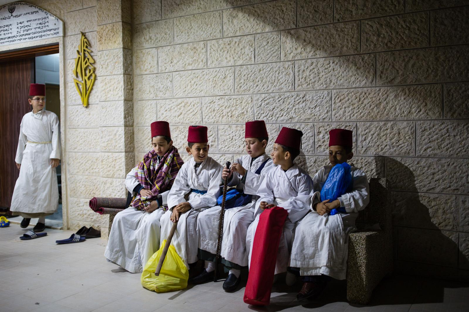 NABLUS, PALESTINIAN TERRITORIES - APRIL 27, 2016: Samaritan children sit outside a synagogue during a pilgrimage marking the holiday of Passover at Mount Gerizim on the outskirts of the West City of Nablus April 27, 2016. The Samaritan religion is descended from the ancient Israelite tribes of Menashe and Efraim, and the community numbers today around 700 people, half at Mount Grizim in the West Bank and the others in Holon near Tel Aviv in Israel.