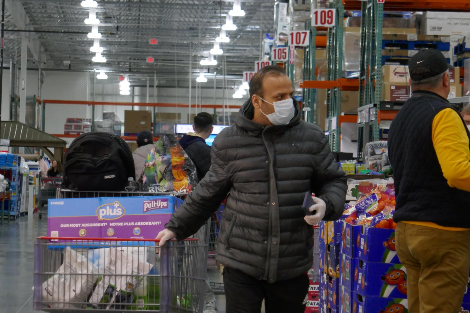 New York - MARCH 19, 2020 - A unidentified man is seen wearing a facial mask and gloves inside a Costco Store Thursday afternoon during the coronavirus pandemic. The coronavirus pandemic may have already thrust the economy into a recession as infections continue to surge, New York has ordered private business to cut on-site workforce by half. (Luiz C. Ribeiro for New York Daily News)
