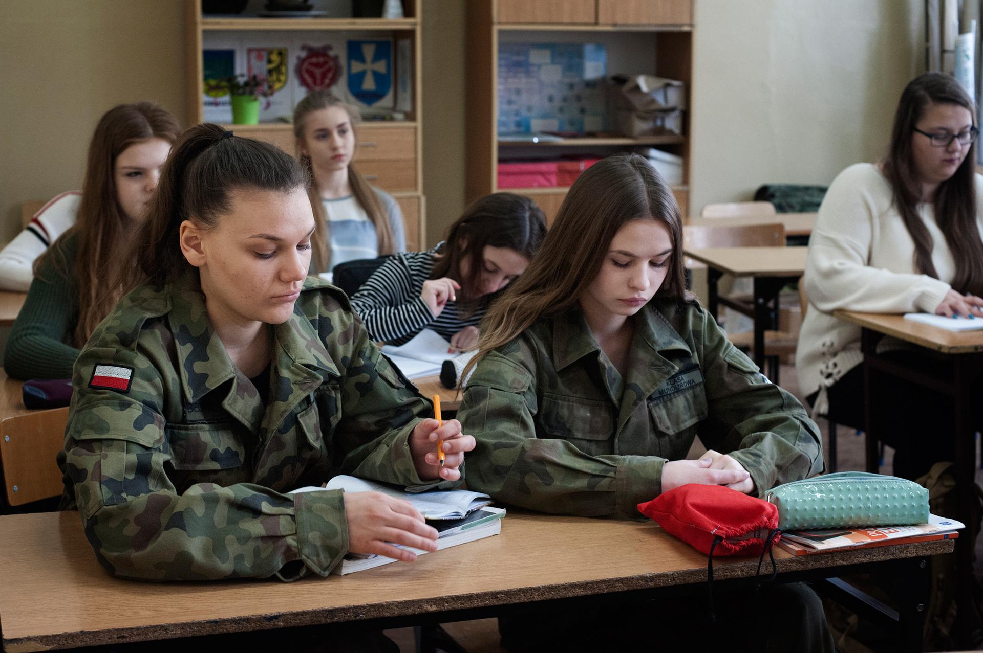 """The 17 years old  students during the history class, the II Public High School in Brzeg. The students who chose """"military profile"""" attend the same classes as those from """"Humanist Profile"""", with the difference that twice a week they have to wear army uniforms. Brzeg 2017 """"Here, no matter how much you study, if you don't have contacts you will not find a job"""" – says Paulina, one of the students aged 17 – """"Many people go abroad, like my cousin, and do not plan to return. If I could have built this country from scratch, work would have been my priority."""""""