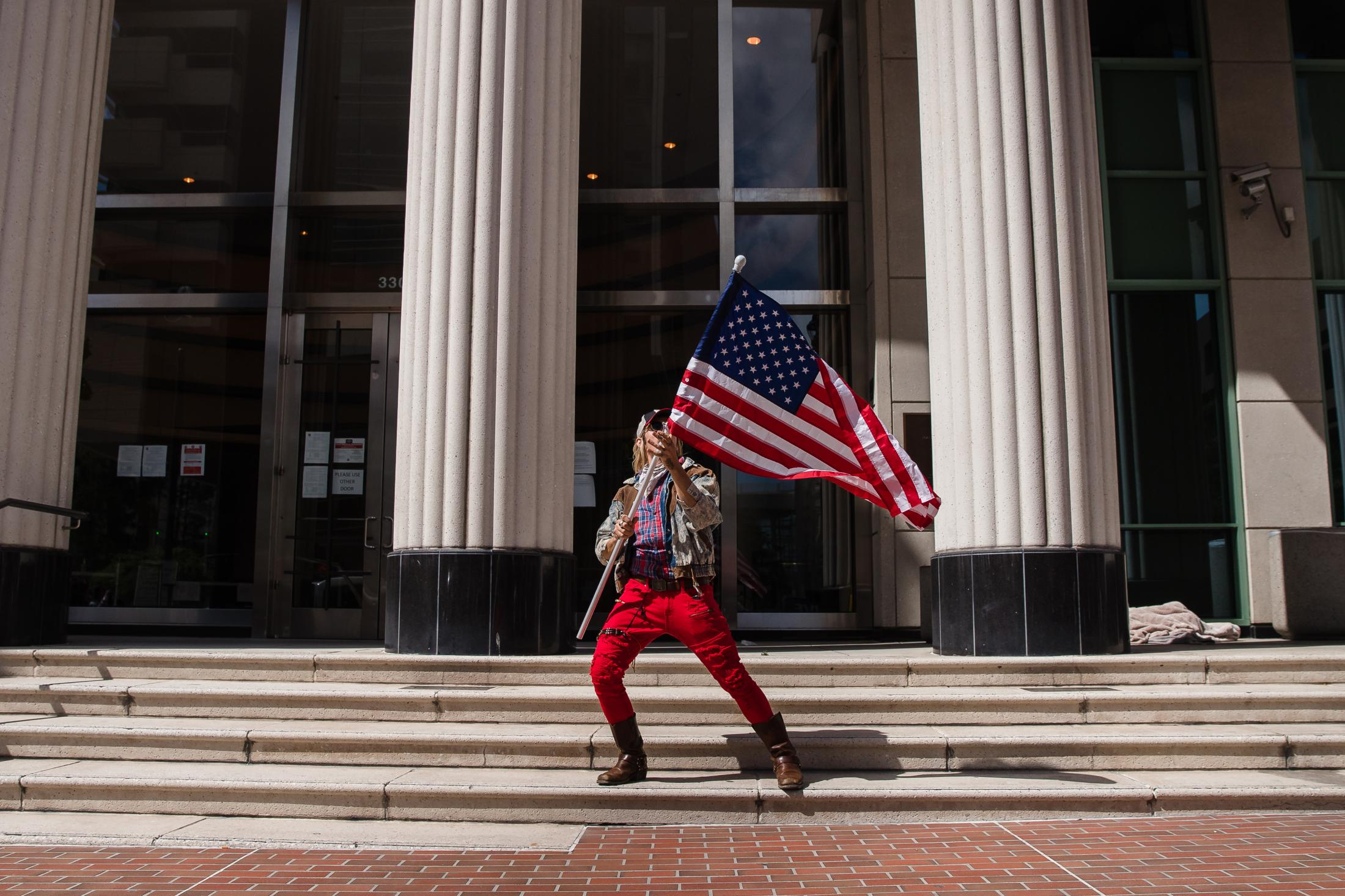 A man waves the American flag in front of the Hall of Justice Courthouse while protesters rally in downtown San Diego against California's stay at home order to prevent the spread of Coronavirus on April 18, 2020. With growing frustration there have been other planned demonstrations in several cities across the United States.