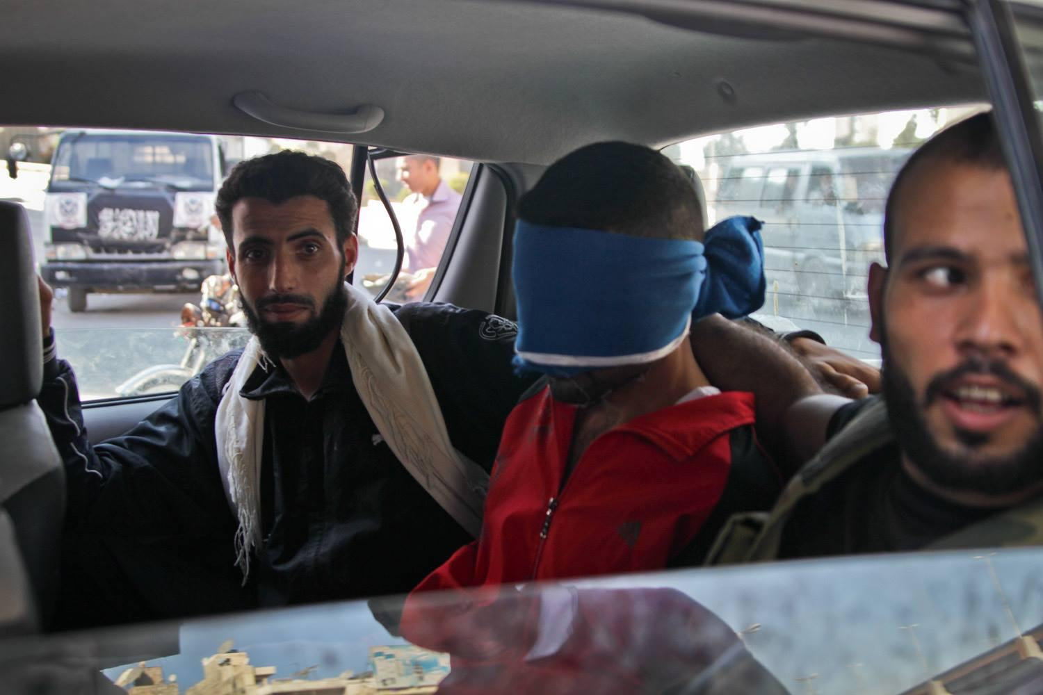 "Near the Free Syrian Army makeshift headquarters, FSA fighters drive through a neighborhood in Aleppo with a member of what they believe to be part of the Shabiha on August 21, 2012. Rebels surrounded the car chanting ""allahu akbar"" (meaning god is great). The man blindfolded was taken to an undisclosed location."