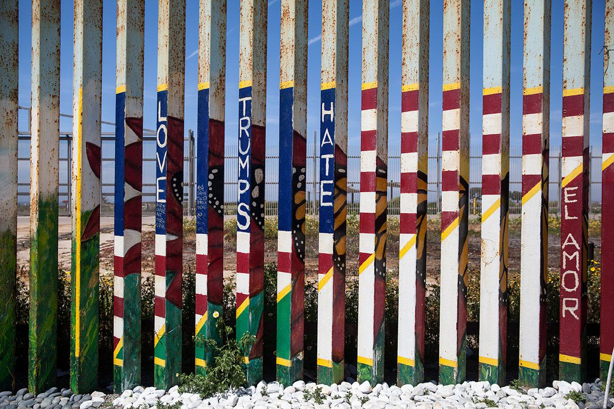 The border fence from the Mexican side is painted with vibrant colors often reflecting the current political climate.