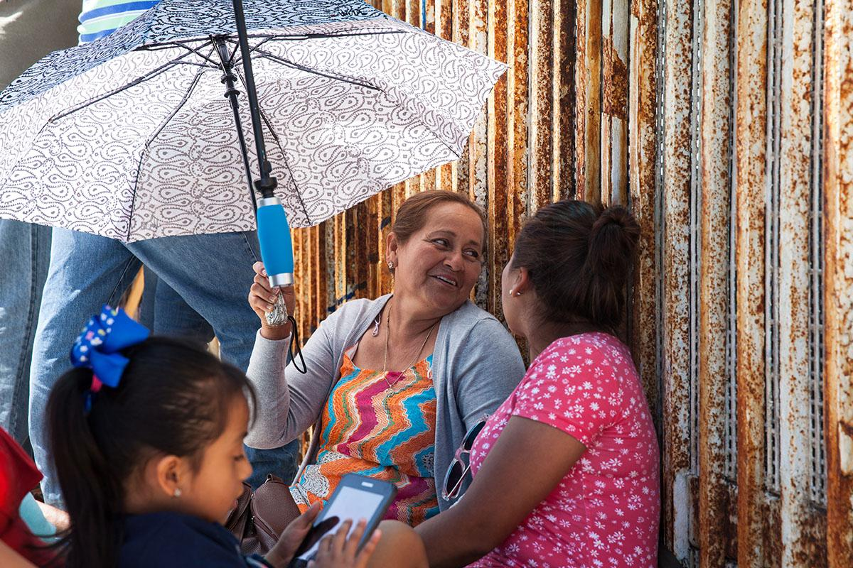 A family at the border fence at Playas de Tijuana, Mexico. A family visits their relative on the U.S. side and talks to them through an open weave metal fence. On the U.S. side there is only a four hour window to visit family members who live in Mexico. There are no restrictions on the Mexican side.
