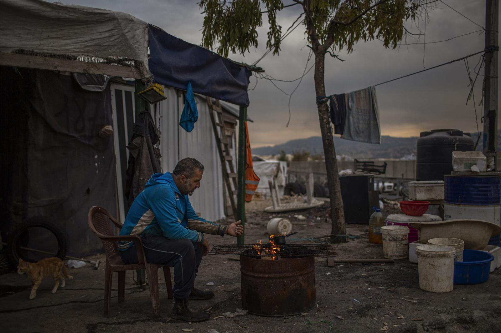 Beirut, Lebanon. November 23th, 2019. A fisherman warms himself early in the morning outside his home at Borj Hammoud port. The Borj Hammoud landfill is currently emanating particularly strong odors. According to air pollution experts, chronic exposure to these strong odors is linked to respiratory diseases, allergies, and the spread of bacteria. Further, experts state that leachate from the Borj Hammoud landfill is being dumped into the sea, polluting the water and making the sea in areas surrounding the landfill dangerous for swimming. Diego Ibarra Sánchez for THE NEW YORK TIMES
