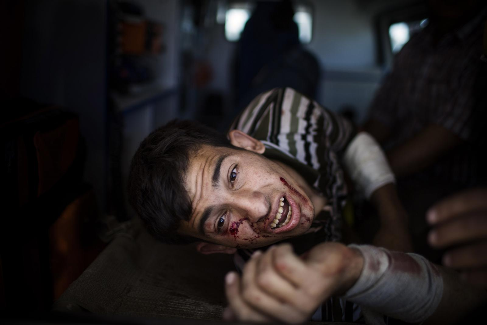 A man injured in a mortar attack lies inside an ambulance after being treated by medics in a field clinic as Iraqi forces battle with Islamic State- Mosul. Iraq, April 2017. Diego Ibarra Sanchez