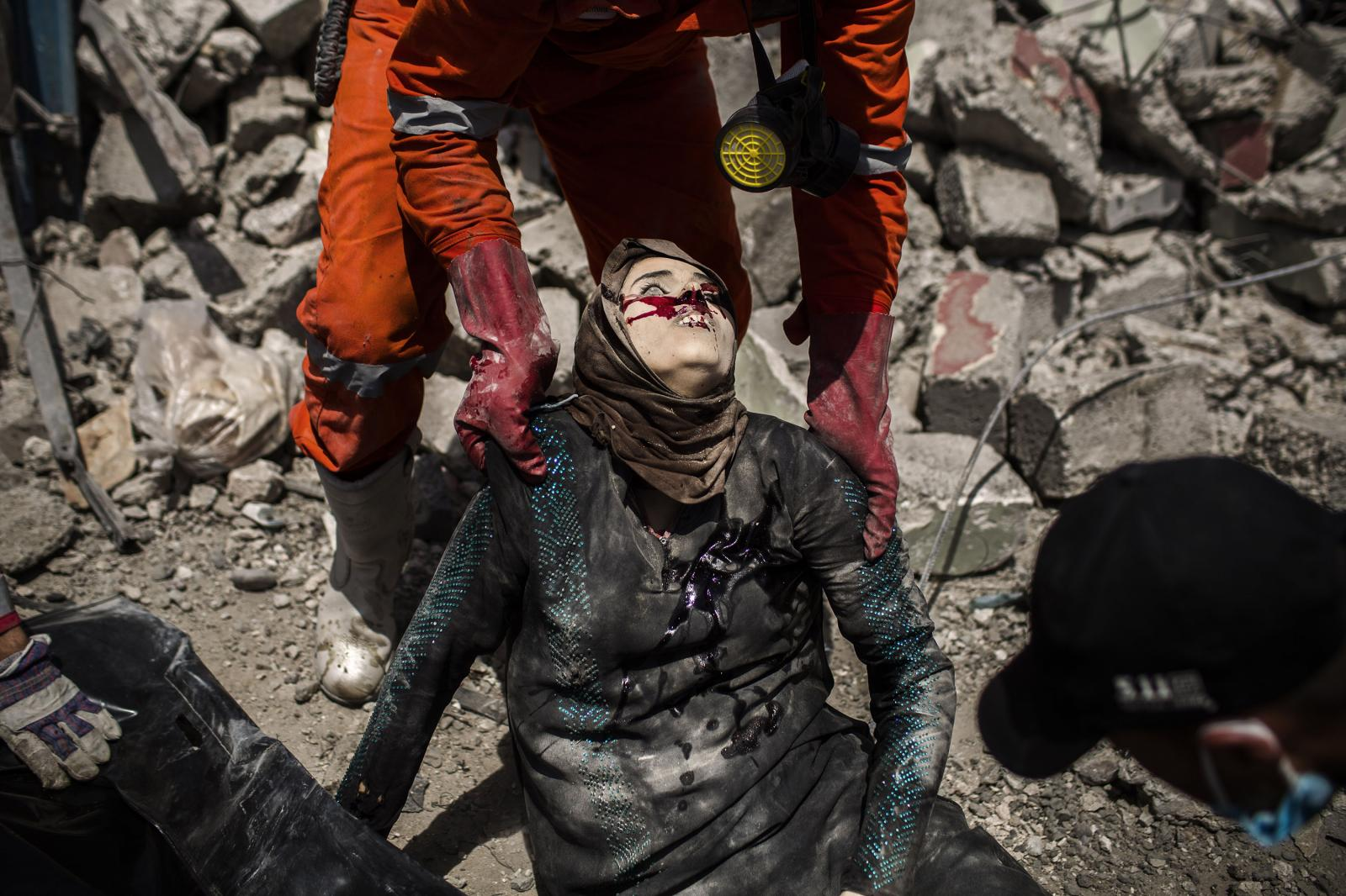 A civil defense team holds the dead body of an Iraqi woman killed after one female suicide bomber blow up herself in Mosul, juts few meters far away from Al Noor Mosque. West Mosul. Iraq. 02/07/2017. Diego Ibarra Sánchez