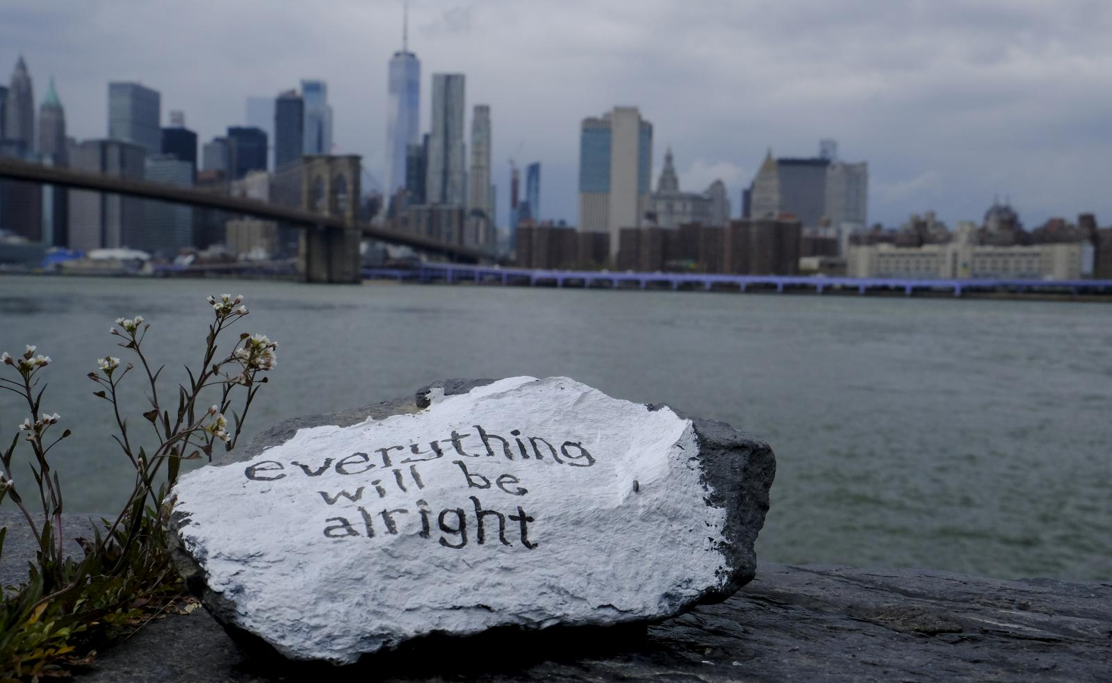 "New York - April 21, 2020 -- Heavy clouds are seen over downtown Manhattan Tuesday afternoon just before the National Weather Service issued a severe thunderstorm warning for New York City. A small stone with the words ""Everything will be alright"" was left by someone on the banks of the East River at the Brooklyn Bridge Park. (Luiz C. Ribeiro for New York Daily News)"