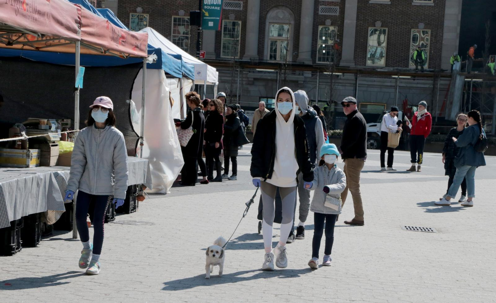 New York - MARCH 18, 2020 - A unidentified family wears facial masks Wednesday morning while strolling on the Union Square farmers. As coronavirus infections continue to surge, New York has ordered private business to cut on-site workforce by half. (Luiz C. Ribeiro for New York Daily News)