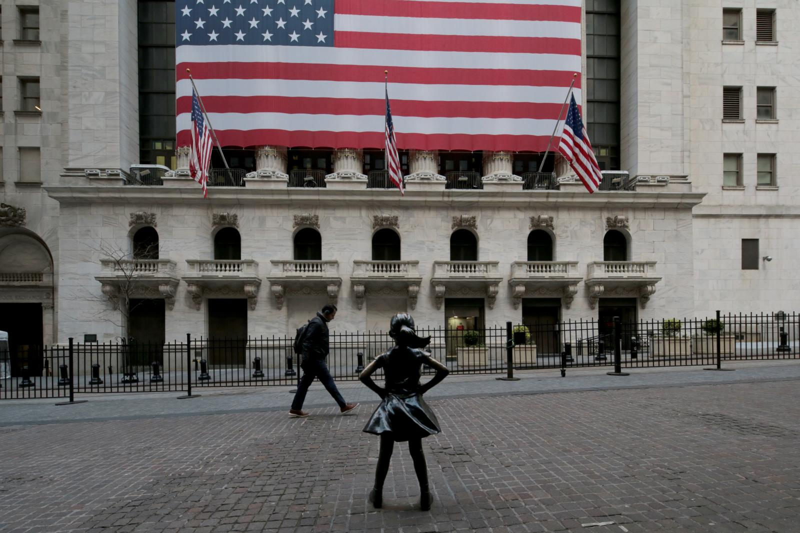 New York - April 22, 2020 -- Fearless Girl a bronze sculpture by Kristen Visbal on Broad Street in front of the New York Stock Exchange is seen wearing a facial mask Wednesday morning during the coronavirus pandemic outbreak. (Luiz C. Ribeiro for New York Daily News)