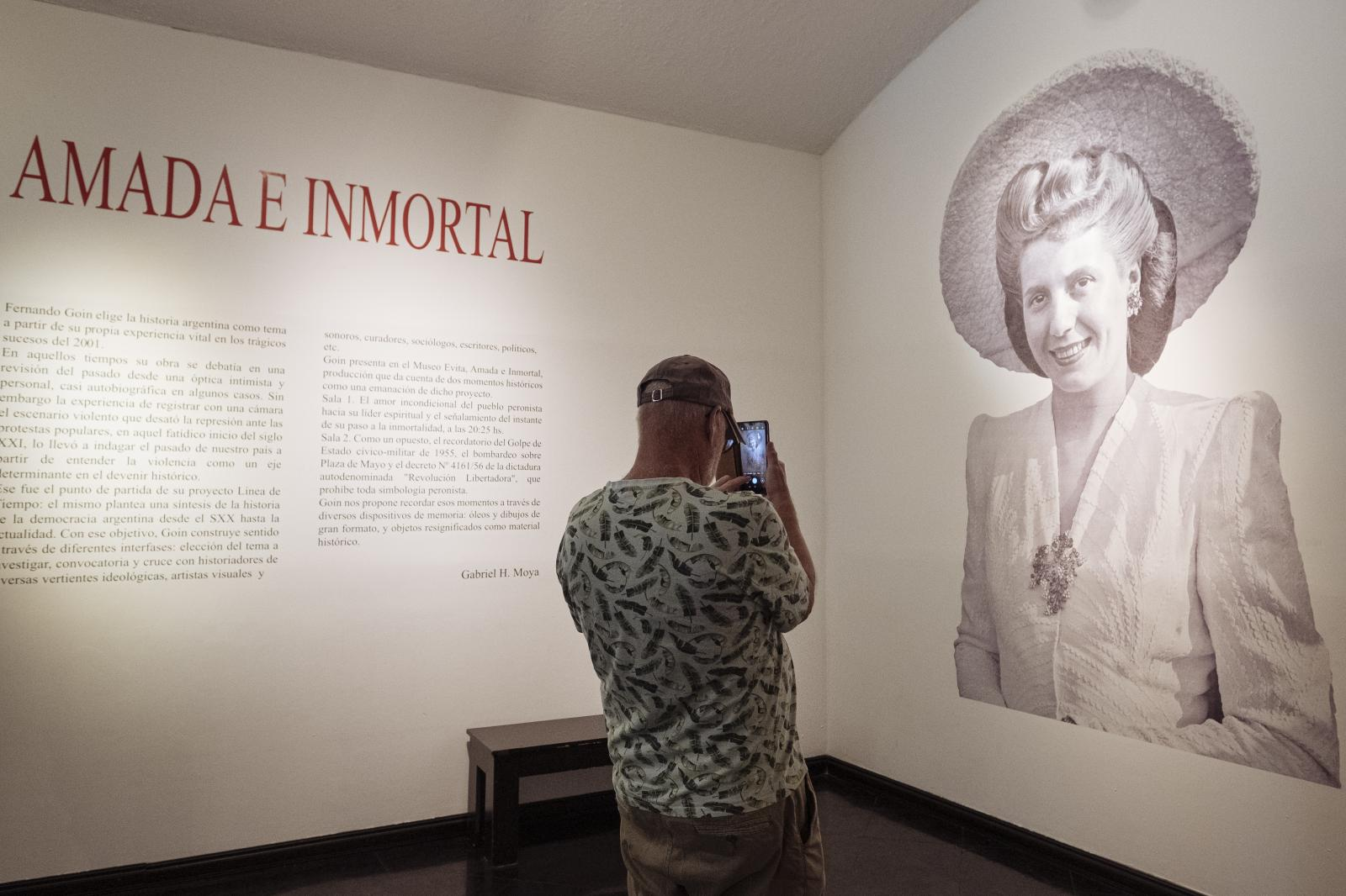 A visitor takes a photograph of an Eva Perón's portrait at Evita's Museum, Buenos Aires, Argentina, on Saturday, Dec. 7, 2019.
