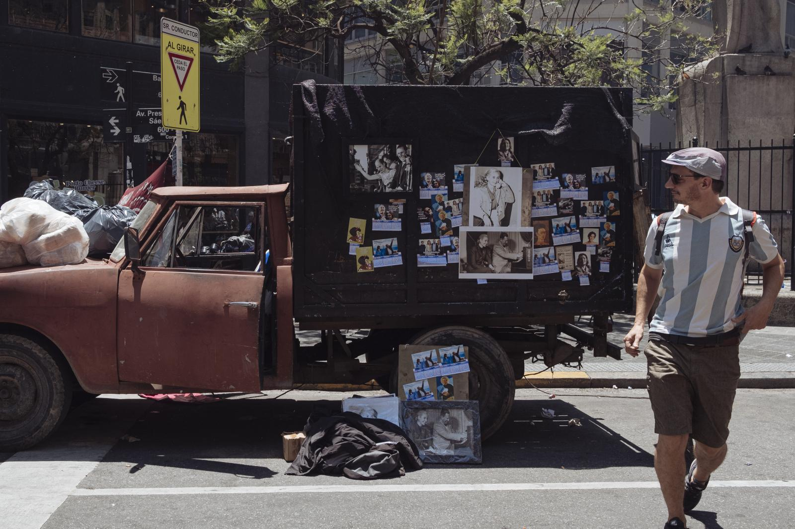 A supporter of Alberto Fernandez with an Argentine football team t-shirt walks in front of a truck with Juan Domingo and Eva Perón's photos on the presidencial swears-in day, Buenos Aires, Argentina, on Tuesday, Dec. 10, 2019.