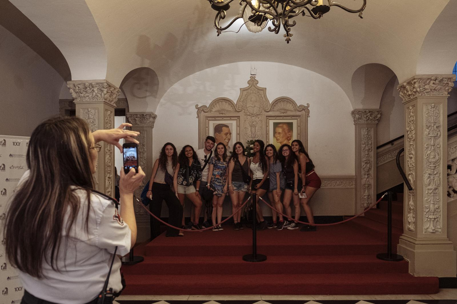 A museum guard takes a photograph of a group of visitors below Juan Domingo and Eva Perón's portraits at Evita's Museum, Buenos Aires, Argentina, on Friday, Dec. 6, 2019.