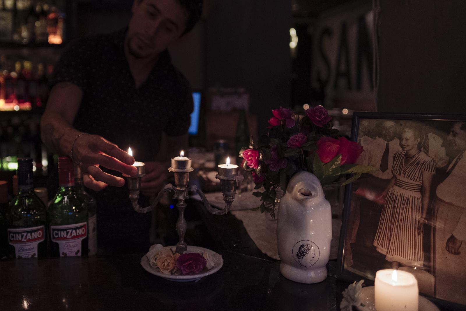 A bartender lights a candle at Santa Evita Restaurant, Buenos Aires, Argentina, on Wednesday, Dec. 4, 2019.