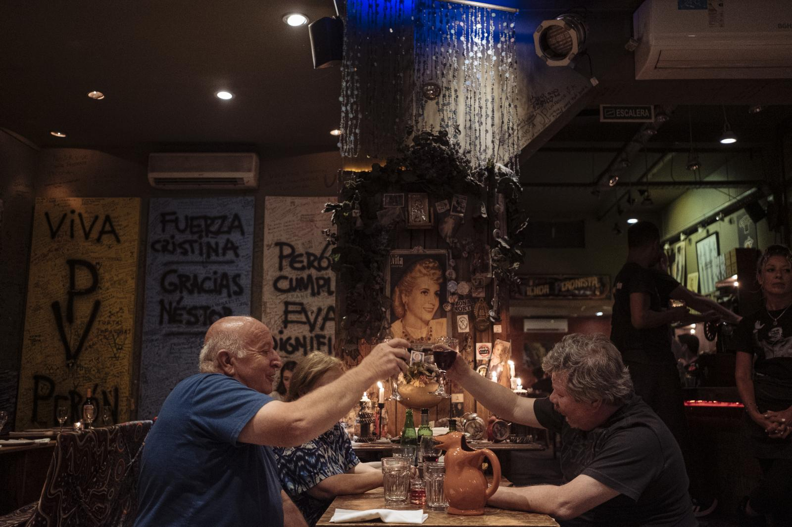 Customers toast in fron of Evita's altar at Perón Perón restaurant, Buenos Aires, Argentina, on Friday, Dec. 6, 2019.