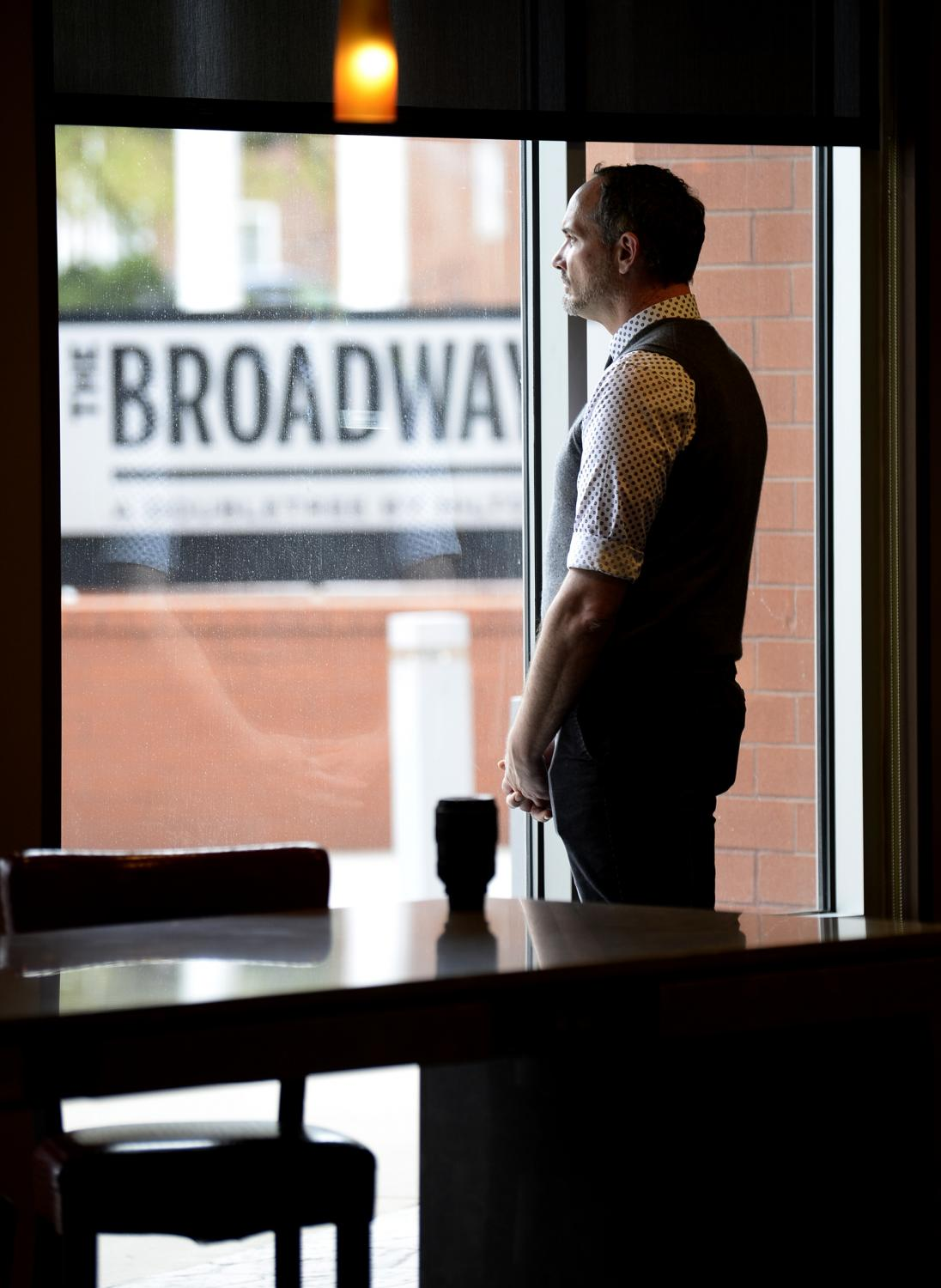 Jeremiah Huey looks out of the window on Wednesday, April 22, 2020, at Broadway Hotel, in Columbia. Huey is the director of nightlife at the hotel. Most of the hotels in town have seen a decrease on its occupancy since the state of Missouri issued the stay-at-home order, due to the COVID-19 situation.