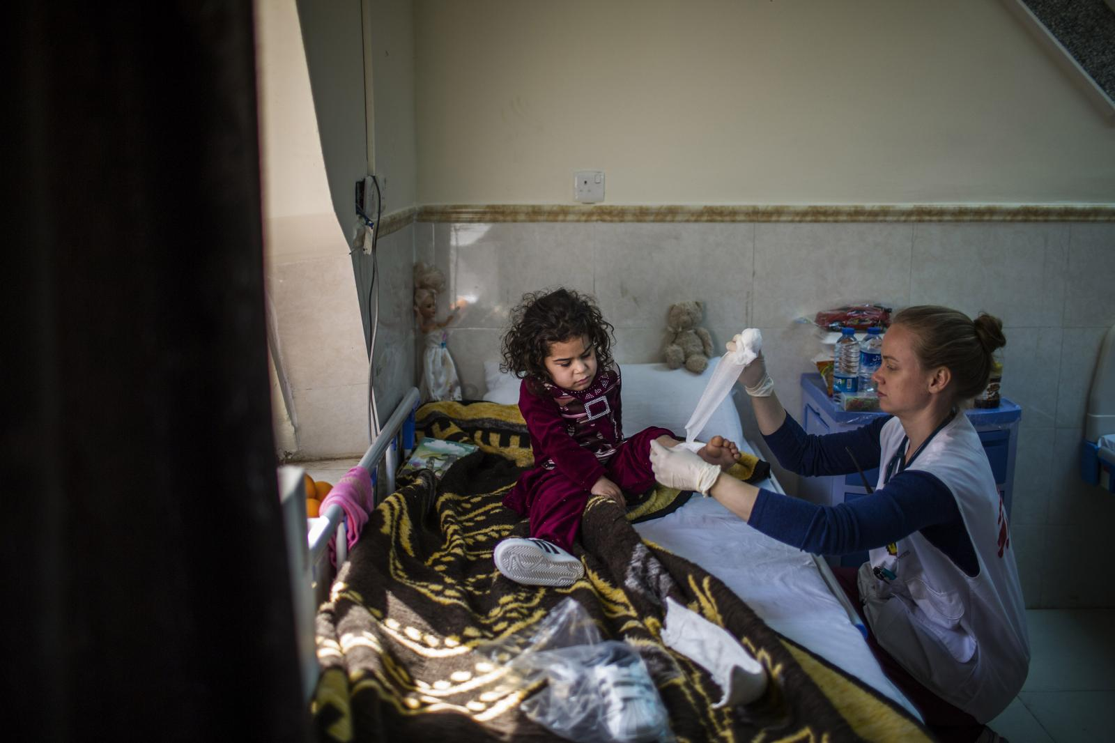 A MSF worker changes the Bandage of Faten, an Iraqi five years old from Mosul. She was injured when she was playing in a garden. She is crying in the night. Hamdaniya, Iraq 2017. Diego Ibarra Sánchez for MSF