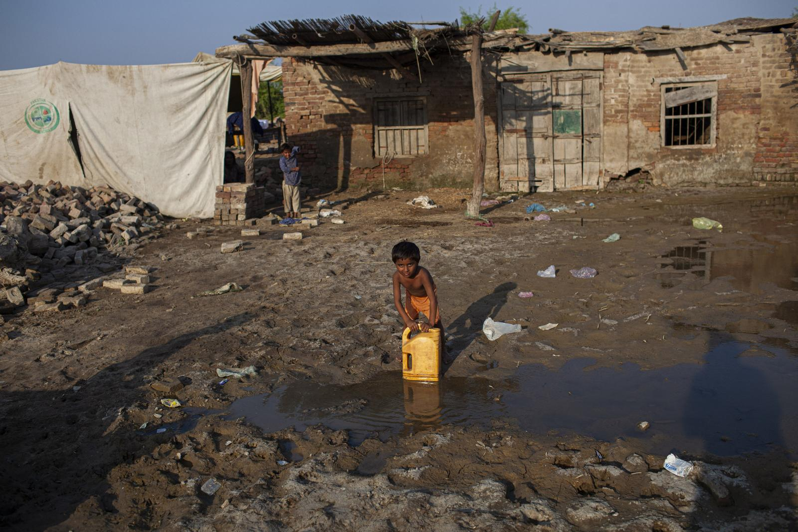 A young Pakistani IPD carries water after the floods in the province of Hyderabad.People's skin is constantly exposed to unsafe water, unhygienic conditions and sharp debris, making skin diseases one of the leading reasons for medical consultations for flood survivors. Diego Ibarra Sánchez for WHO