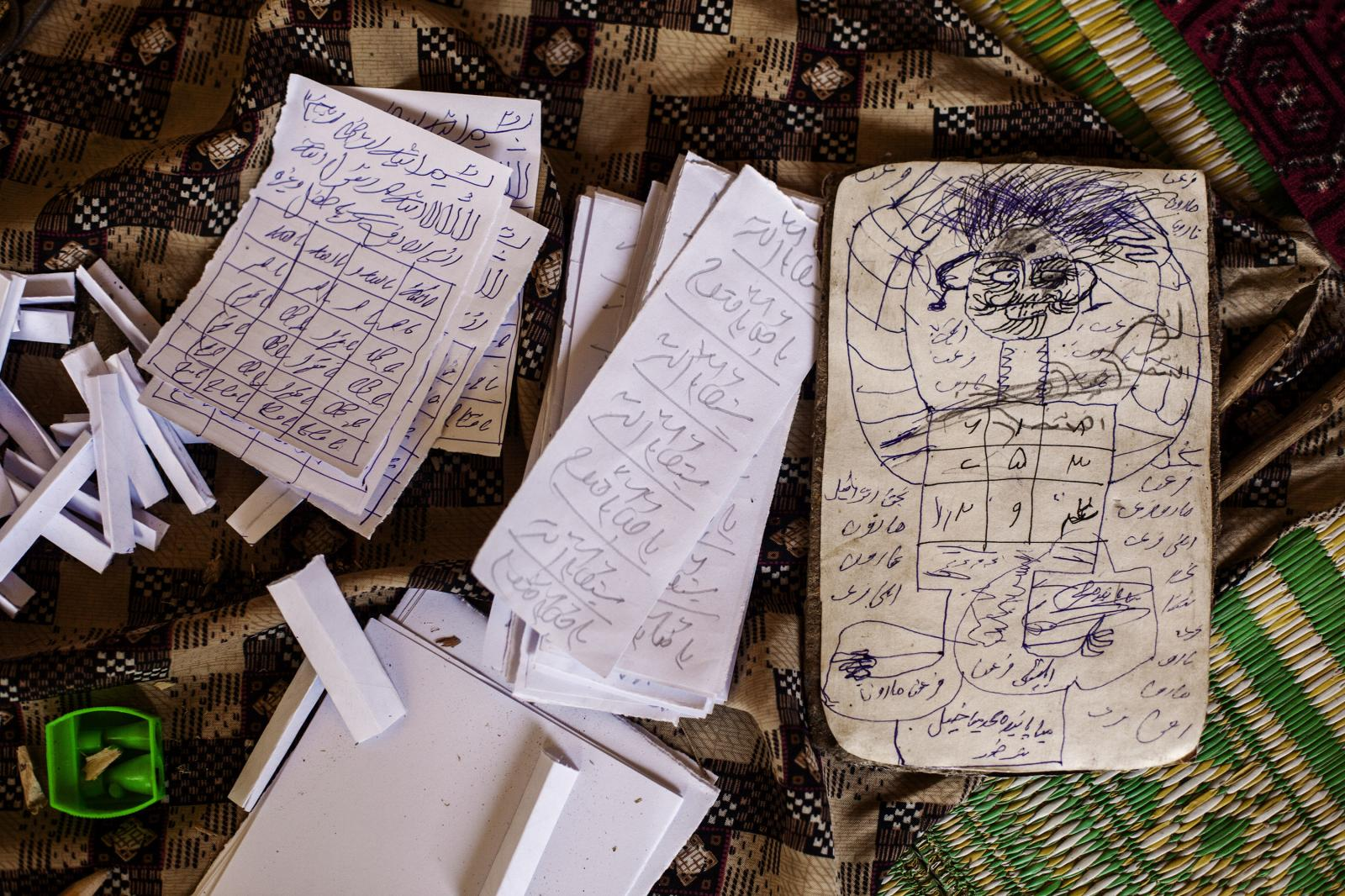 write words (TAWEEZ or SHOHEST) on pieces of paper that are burnt after the healing process is finished. Jajalabad, Afghanistan. April 30th, 2014. Diego Ibarra Sánchez / MeMo The mental health situation in Afghanistan is characterized as an extremely incapacitated mental health care system