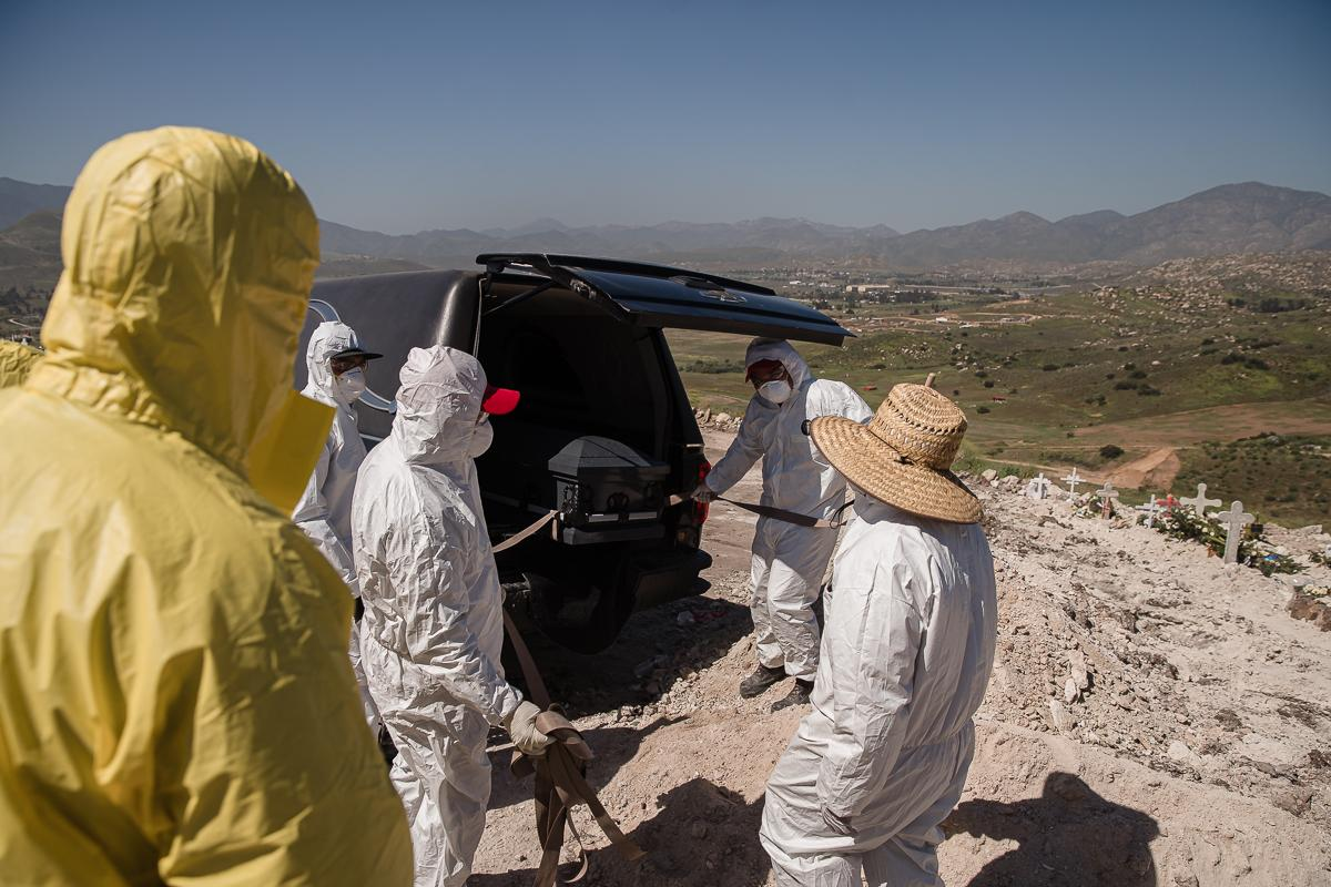 Gravediggers get ready to carry a coffin to a burial plot at Tijuana Municipal Cemetery No.13 of Jesus Osario Flores who died from coronavirus (COVID-19) on April 24, 2020.