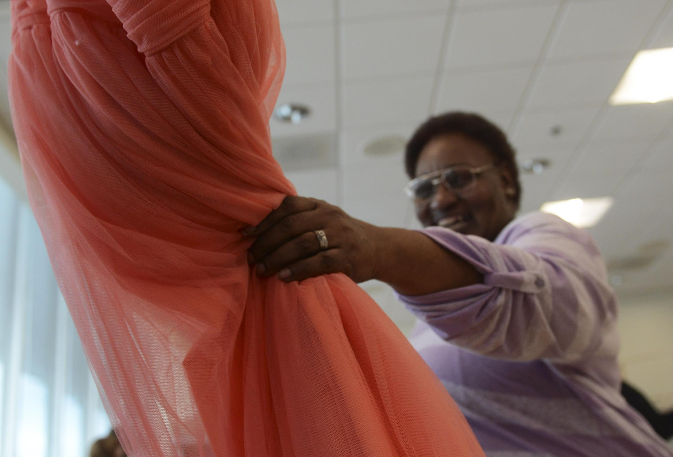"""Donna Fullington hands off her dress to a volunteer at the 'Say Yes to the Dress' event on Saturday, Jan. 25, 2020, at the Activities and Recreation Center. """"It is everything I could have imagined,"""" Fullington said. """"I am as happy as a little tree bird."""""""