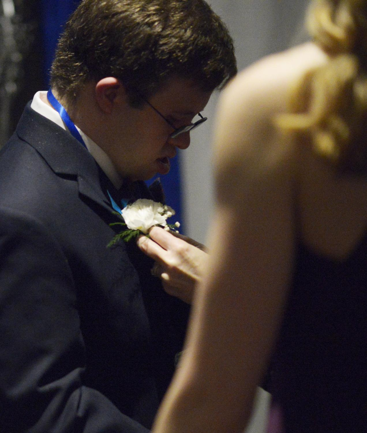 Christopher Mussatt receives a white boutonnière from event volunteer Betsy Borsheski on Friday, Feb. 7, 2020, at The Crossing in Columbia. Every guest was given a corsage or boutonnière upon arriving.