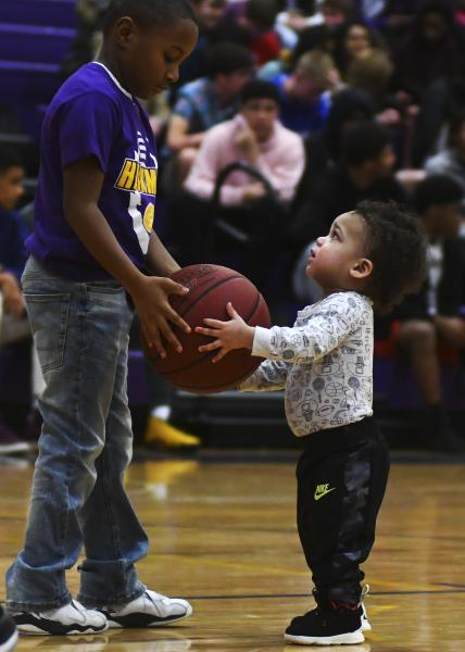 From left, 8-year-old Caleb Smith and 17-month-old Lachlen Alvis play with a basketball at the Hickman Kewpies and Vashon Wolverines game on Saturday, Feb. 15, 2020, at Hickman High School.