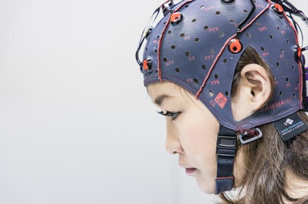 Kyoto, Japan, January 2019. PhD Minaka Homma testing a neural helmet for an experiment regarding the BMI third arm, inside ATR laboratories. Thanks to the third arm it will be possible to enhance human capabilities, mental cognition, and to control different skills at the same time.
