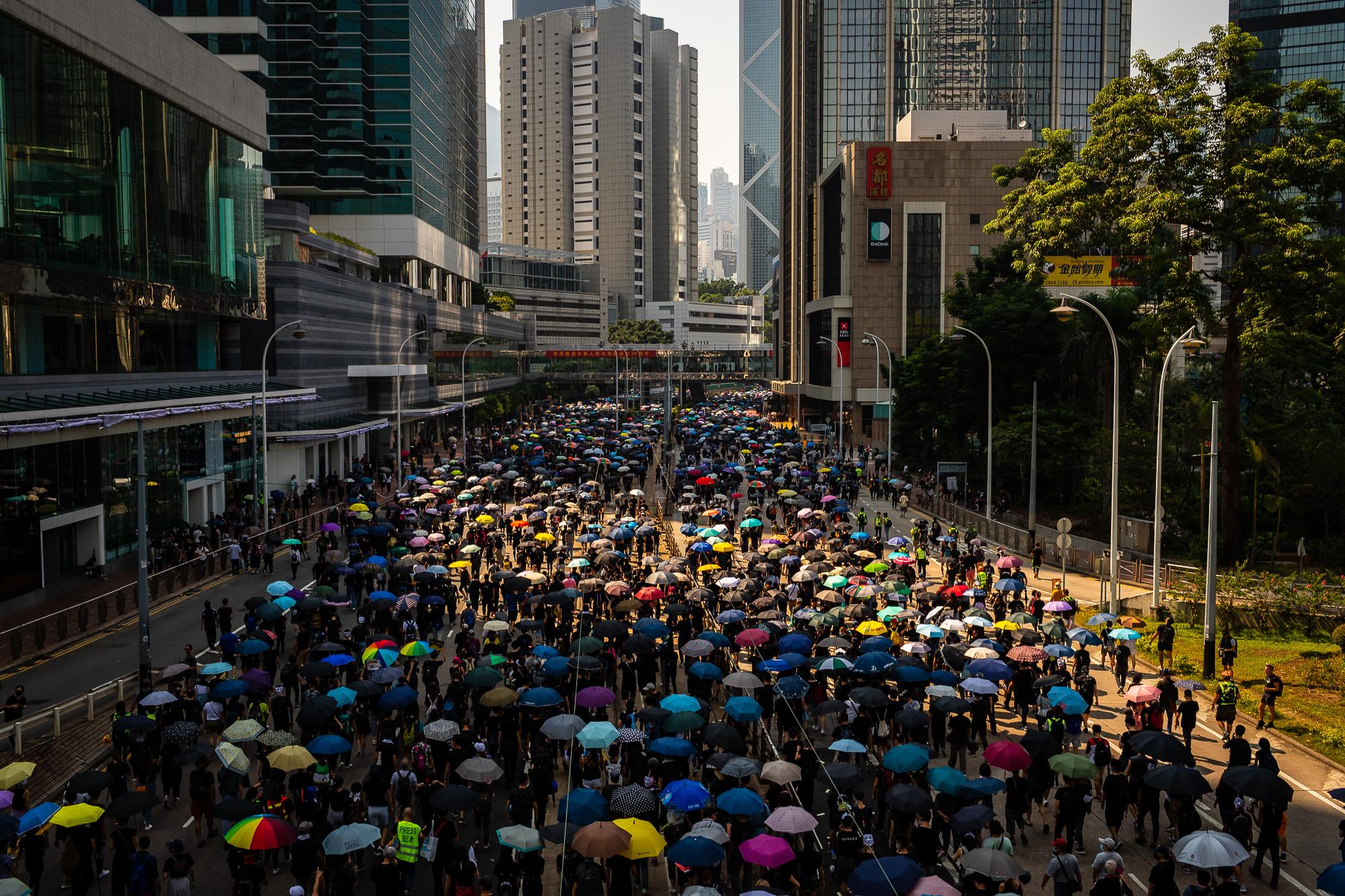 Demonstrators march with umbrellas during the protest in Hong Kong during the holiday marking 70 years of Communist rule in China began in Beijing.