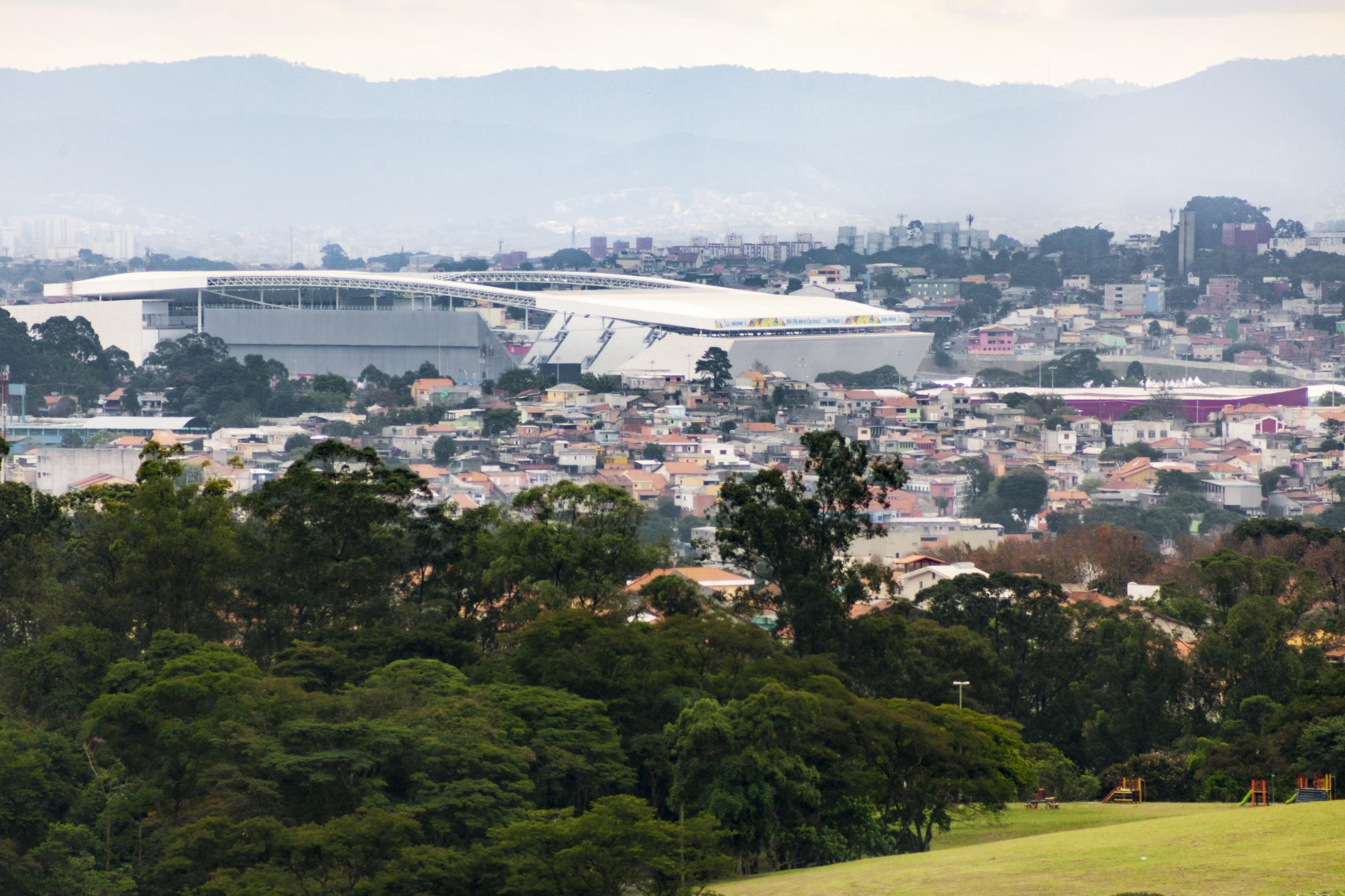 The 'Arena Corinthians' stadium, located at the Itaquera neighborhood,  seeing from the top of a hill at the MTST's shacks camp, located 3 miles away. Itaquera, São Paulo / Brazil. 2014.
