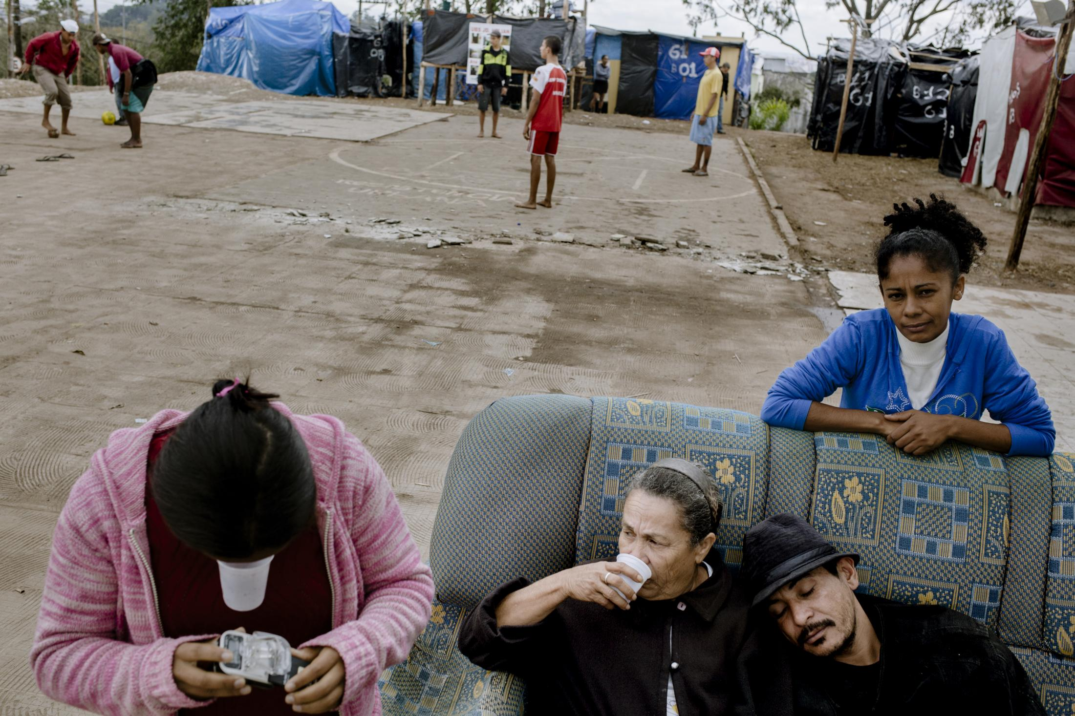 A group of neighbors relaxing after a day of labor at the MTST camp. About 5000 people settled here demanding housing rights solutions, while the country spent $3.6 billion on construction, logistics, and marketing, using public funds. Itaquera, São Paulo / Brazil. 2014.