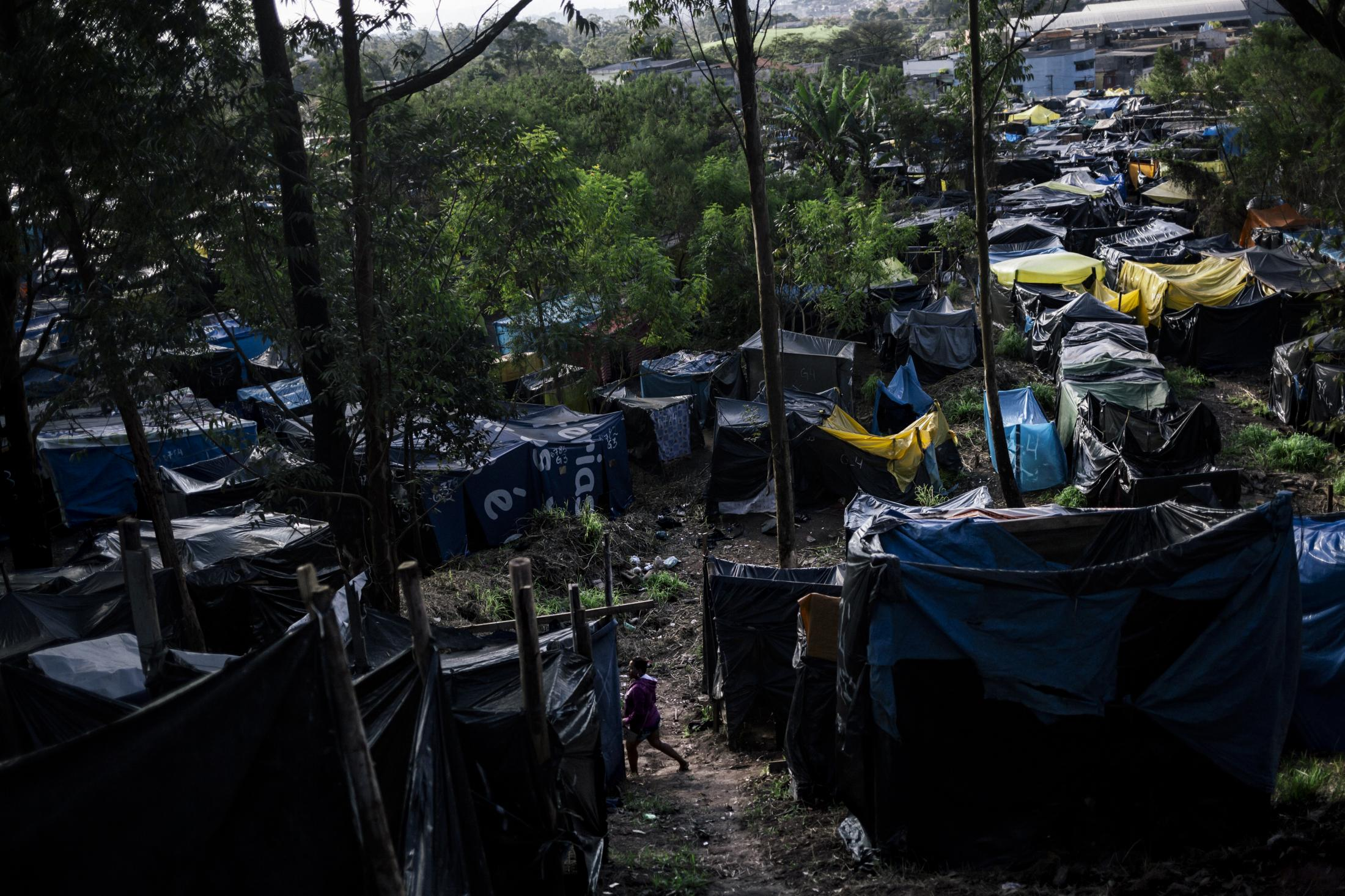 A woman passes by an improvised corridor among hundreds of shacks where families sleep on the abandoned lot with 34 acres of extension. Itaquera, São Paulo / Brazil. 2014.