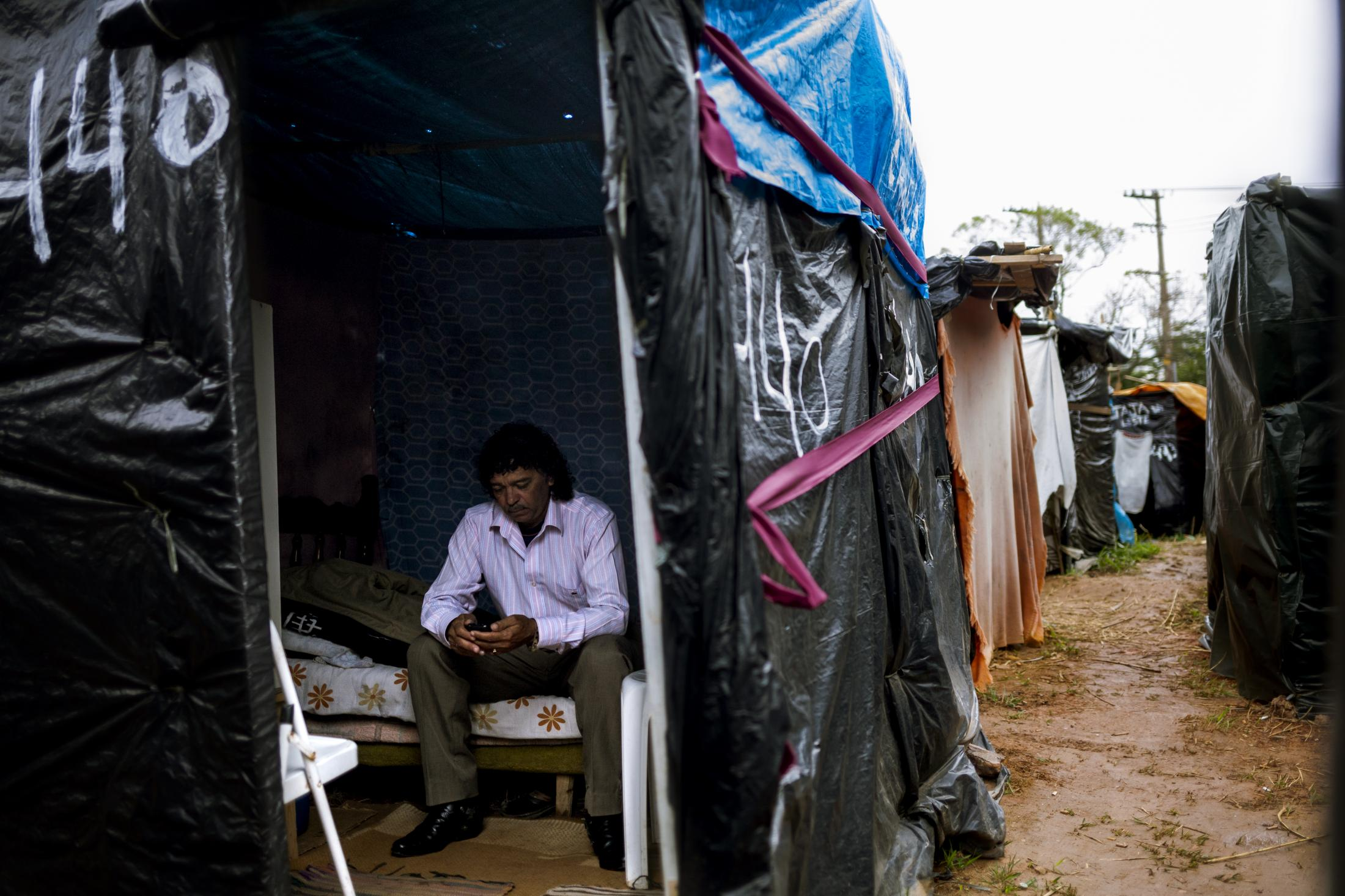 A man is sitting pensively inside his 6x6 shack. Between 2011 and 2014, about 200.000 people reported eviction as a result of building works for the Brazilian World Cup. The official numbers provided by the government did not even reach the 40.000. Itaquera, São Paulo / Brazil. 2014.