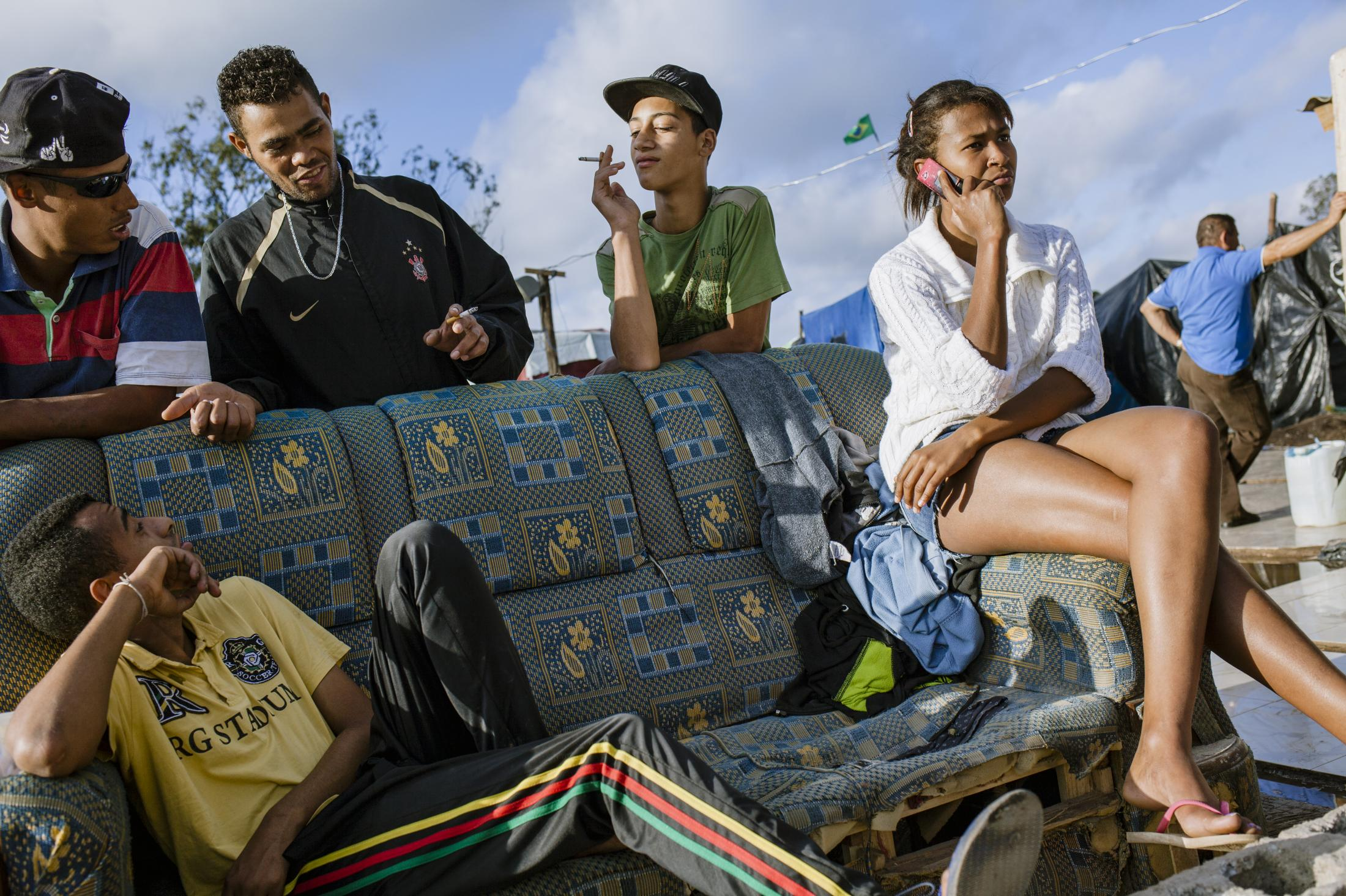Teenagers passing cigarettes around, gathered at the main entrance of the camp. A proposed eviction of the 'Favela de la Paz,' located in the same area where the stadium is, was prevented by the action of these groups and negotiations with the municipality. However, more than 4000 people ended up being evicted, in another nearby area that connected the highway with the airport, bringing those groups to the campsite in Itaquera. Itaquera, São Paulo / Brazil. 2014.