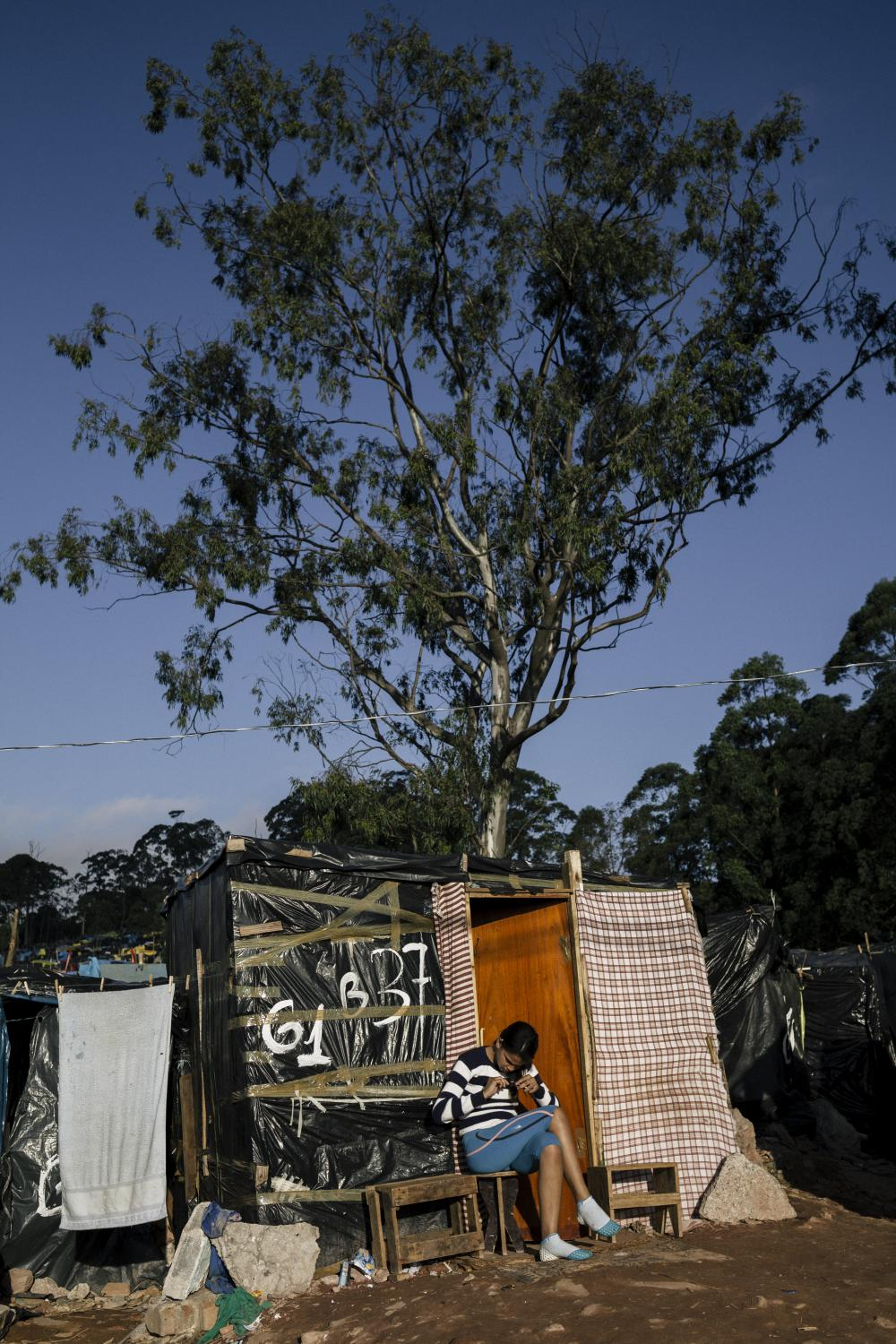 A teenage girl sits outside her improvised house, on the outskirts of the camp. Itaquera, São Paulo / Brazil. 2014.