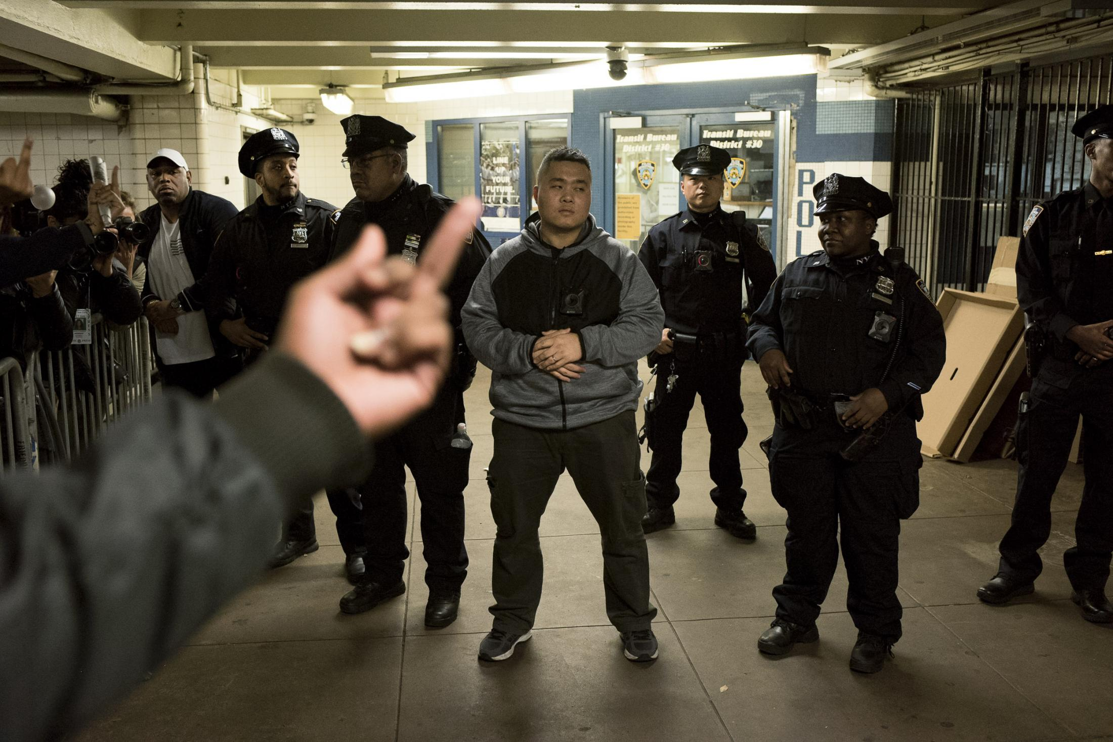 A group of NYPD officers standing at one of the exists of Hoyt station, while protesters yell and show them signs of anger and disgust. Brooklyn, NY. November 2019
