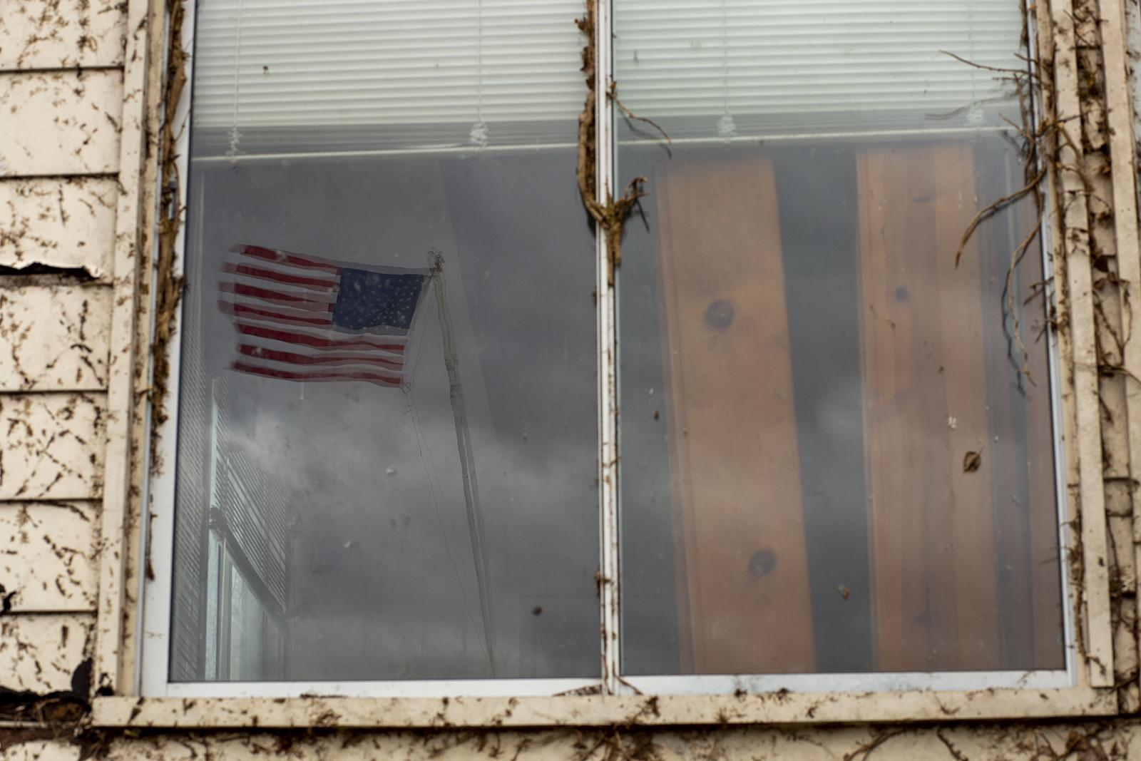 HARPERS FERRY, WV - FEBRUARY 7: The American flag reflected in a window of some of the ruins of the Hilltop House Hotel complex in Harpers Ferry, WV. Some kind of hotel has been atop the bluff overlooking the town since 1888. How to redevelop the current hotel and surrounding land has created deep divisions among the residents of Harpers Ferry. (Photo by Robb Hill for The Washington Post)