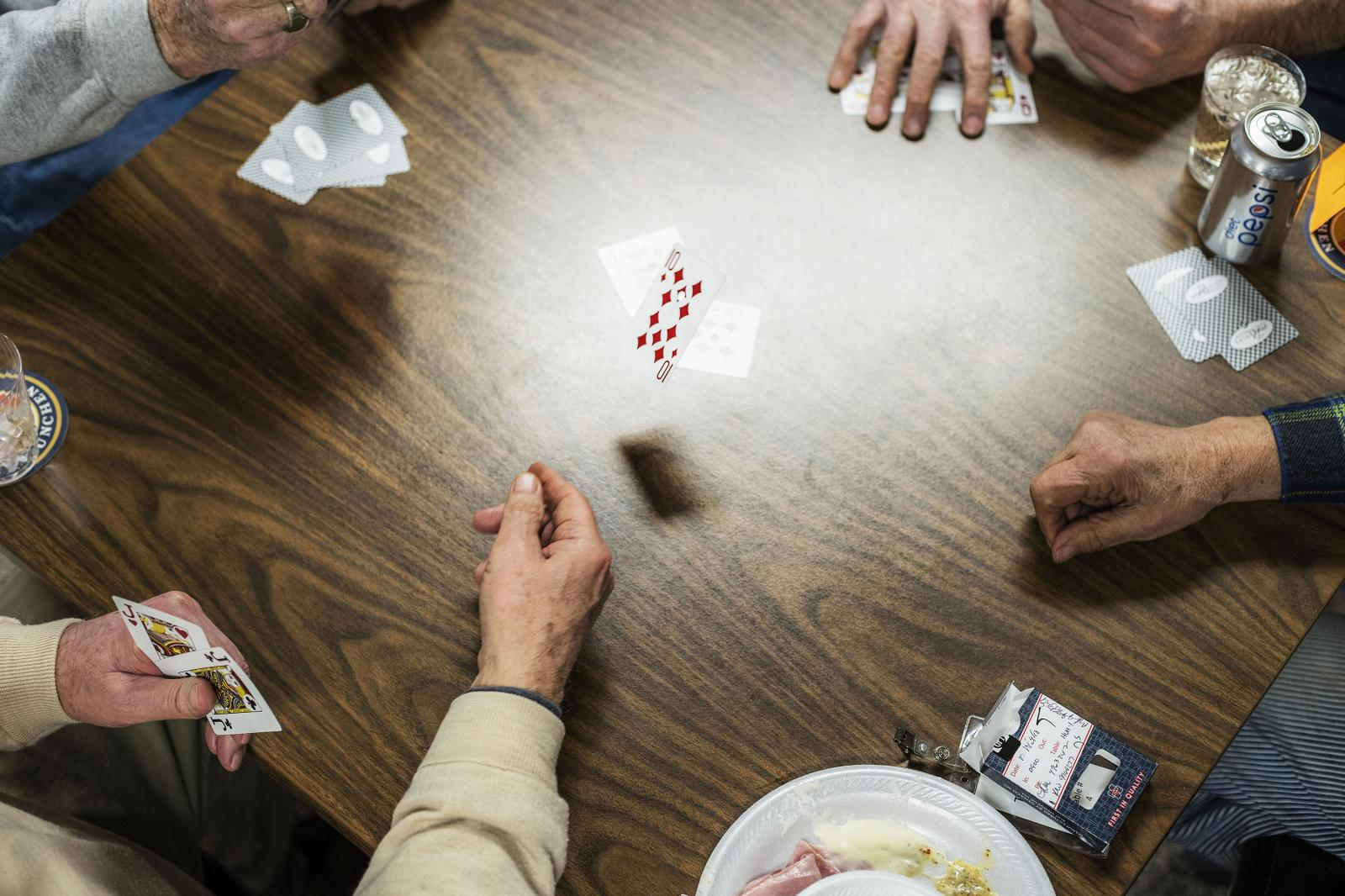 Jim Neswold of West Branch lays a ten of diamonds during a community euchre game night at the American Legion hall in Lone Tree on Wednesday, March 6, 2019. KC McGinnis for The Gazette