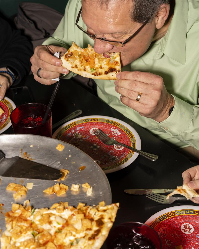 Dave Pope of Grinnell, Iowa eats the popular crab rangoon pizza at Fong's Pizza in Des Moines, Iowa on Saturday, January 18, 2020. KC McGinnis for Buzzfeed News