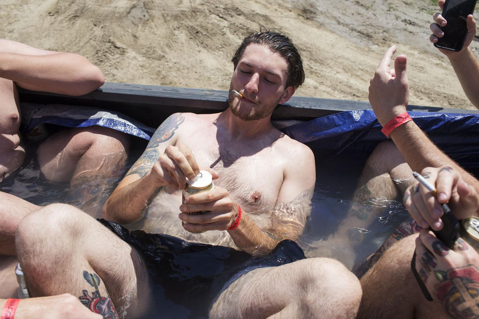 Alic Scoat drinks a beer in a pool made out of a pickup bed during Audiofeed Festival in Urbana, Illinois on Saturday, July 1, 2017. The party was later broken up by security; Audiofeed is an alcohol-free festival. © 2017 KC McGinnis