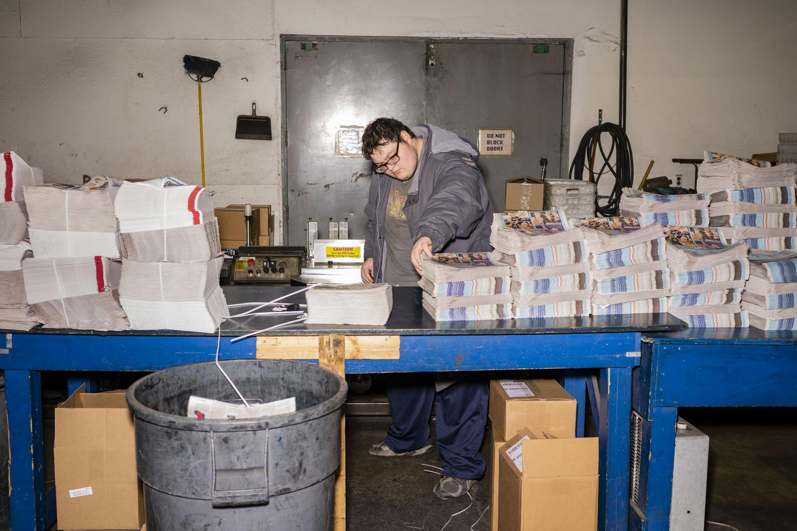A press worker looks over papers in the printing room of the Creston News Advertiser in Creston, Iowa on Friday, December 13, 2019. KC McGinnis for La Croix L'Hebdo