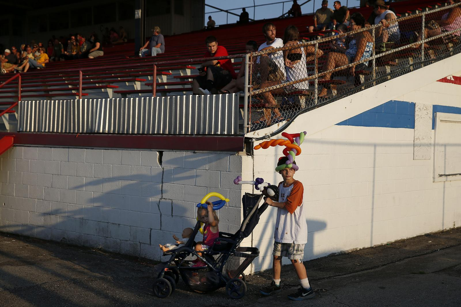 11-year-old D.J. McKinney of Cedar Rapids pushes his one-year-old sister Sofia McKinney in a stroller during race night at Hawkeye Downs in Cedar Rapids on Friday, August 14, 2015. (KC McGinnis / The Gazette)