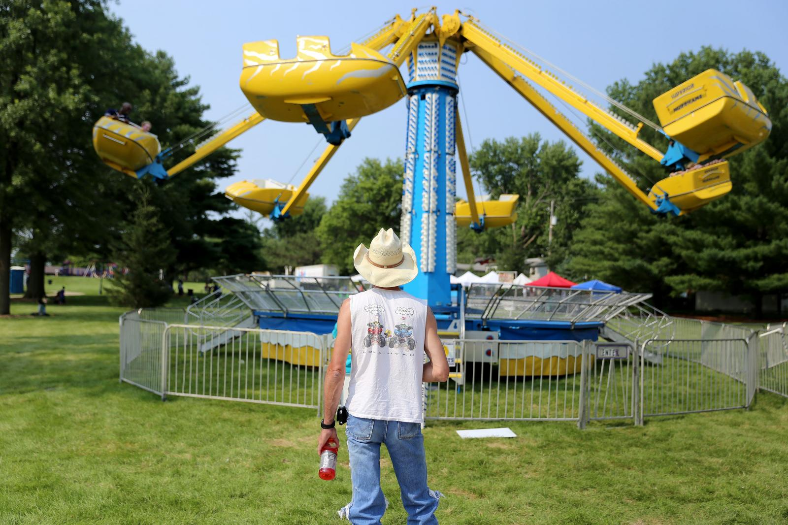 Rick Muller, of Iowa City, waits for his daughters and nephew to finish riding a carnival ride at the Coralville 4thFest at S.T. Morrison Park on Friday, July 3, 2015. (KC McGinnis / The Gazette)