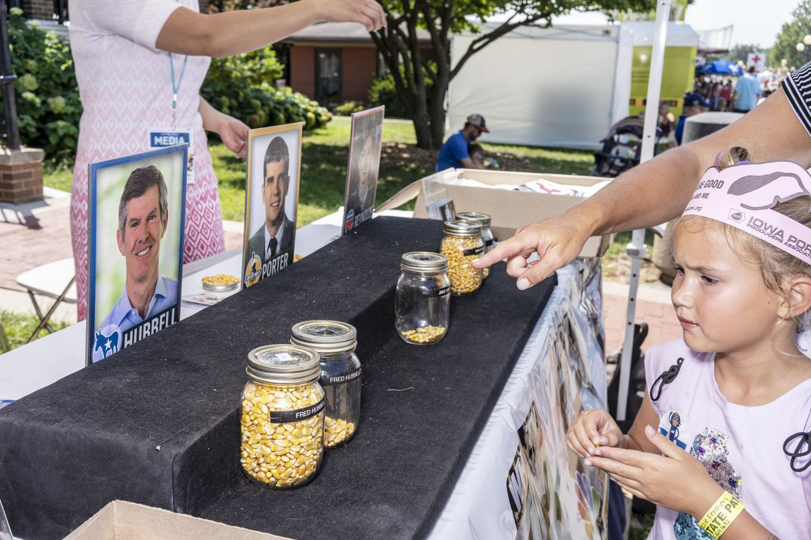 A parent points to a seed jar representing votes for Iowa gubernatorial candidate Fred Hubbell at the Iowa State Fair at Des Moines, Iowa, U.S. August 9, 2018. REUTERS/KC McGinnis