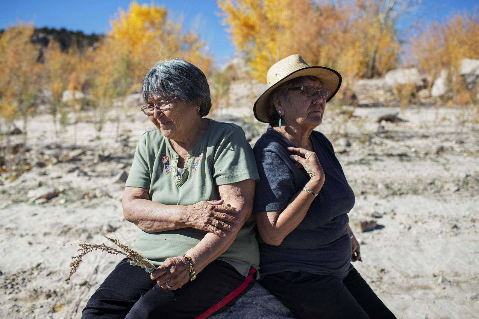 BLANDING, UTAH - OCTOBER 27, 2017: Sisters Louise Jensen and Irene Clah sit on a rock along a reservoir near Bears Ears National Monument land outside Blanding, Utah on Friday, October 27, 2017. Jensen and Clah, Navajo people who grew up in the area, expressed doubts that Bears Ears' monument status will protect their way of life, instead showing concern that the monument's popularity with tourists may cause greater interference with the land. CREDIT: KC McGinnis for The New York Times