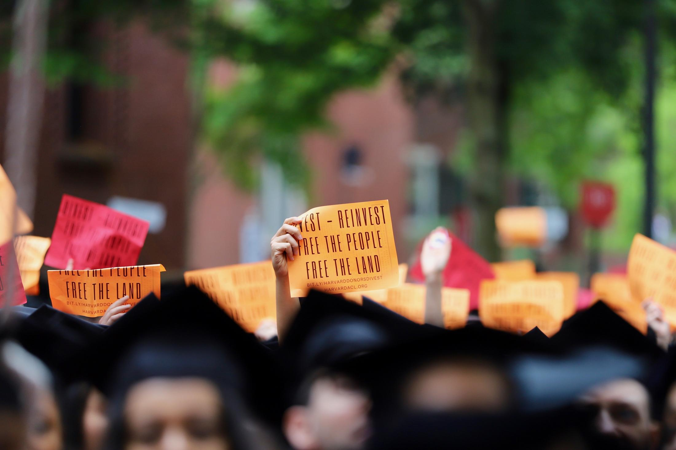 Protestors raised signs demanding that Harvard Divest from Fossil Fuels during Harvard Commencement ceremony in 2019.