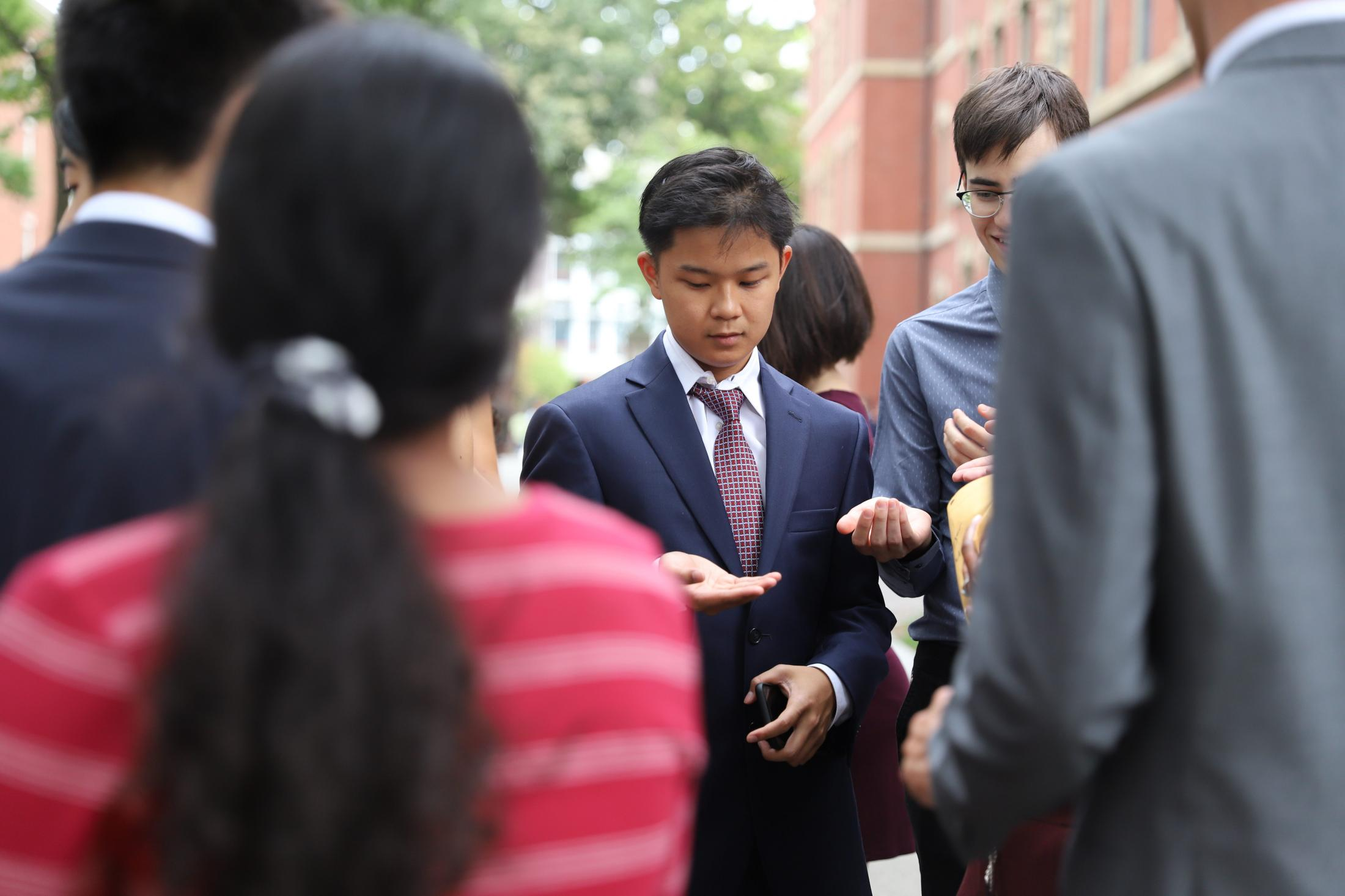 A freshman receives his class pin before Convocation in August 2019.