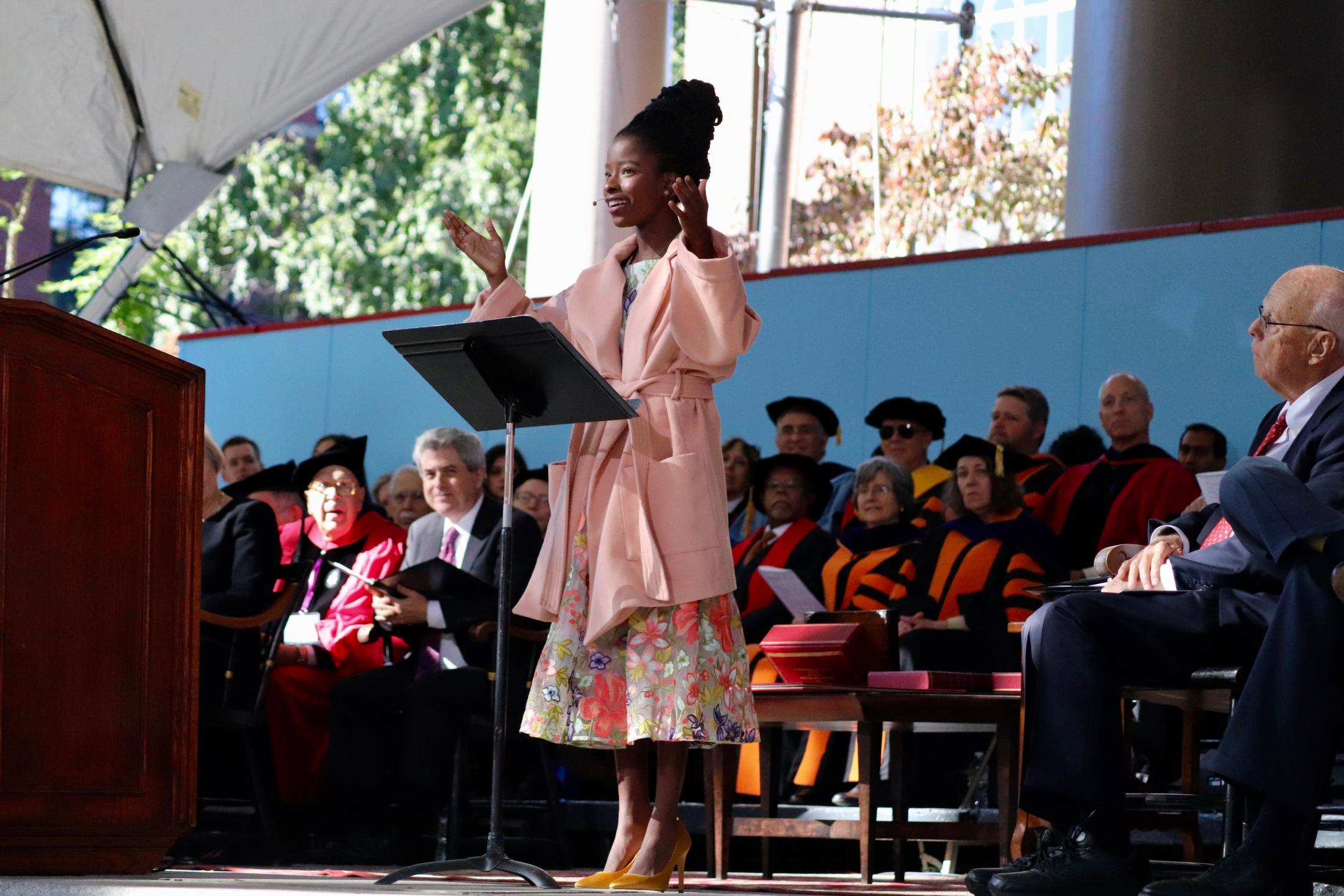 Amanda S.C. Gorman '20, the inaugural Youth Poet Laureate of the United States, raises her hands to the crowd while delivering an original poem that she wrote specifically for President Bacow's inauguration.