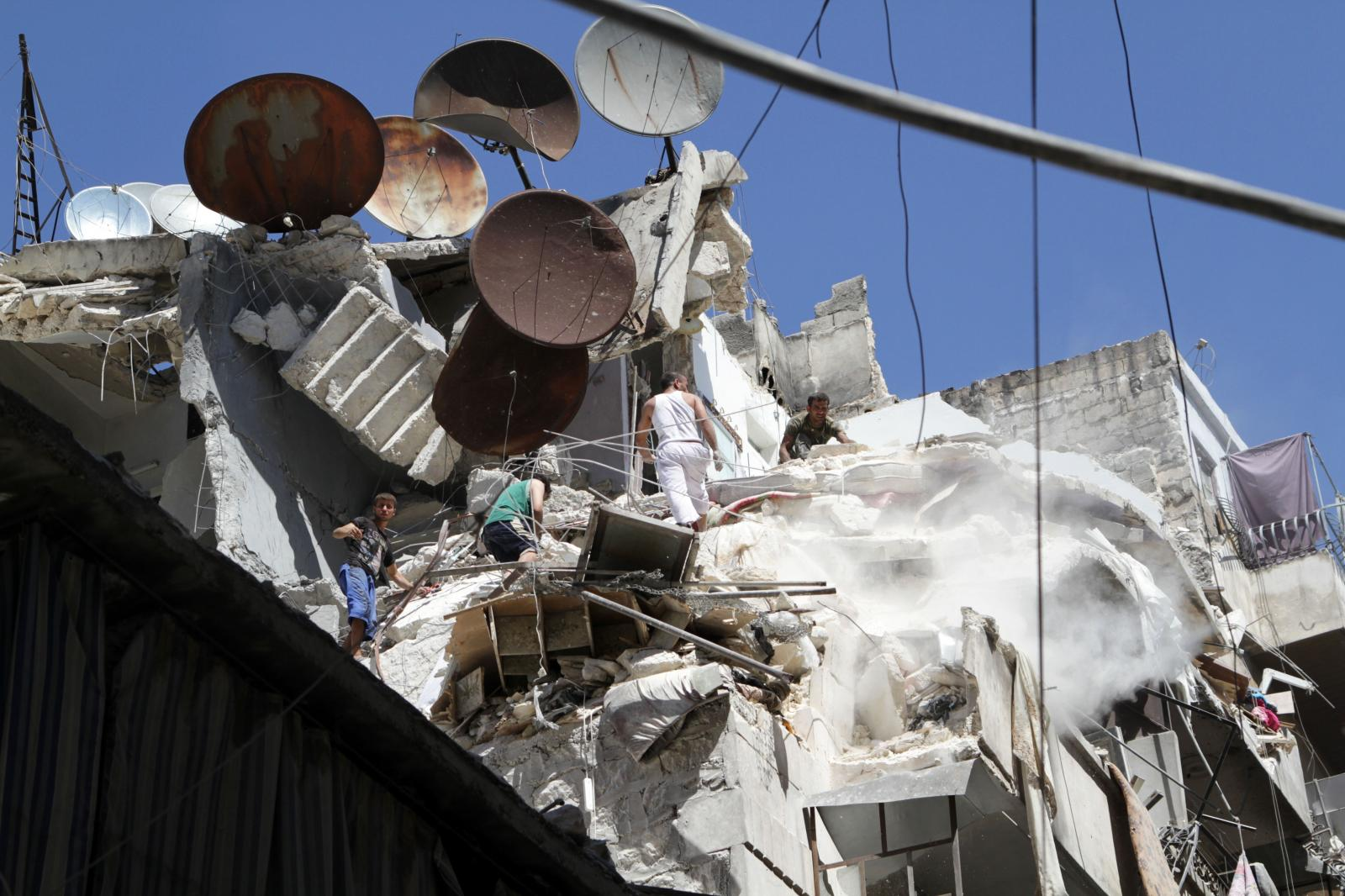 An aerial bomb targeted an apartment building by Assad's forces where a couple lived, decimating their apartment on August 23, 2012. Residents in a neighborhood in Aleppo help search for the husband. The wife was found and killed instantly.